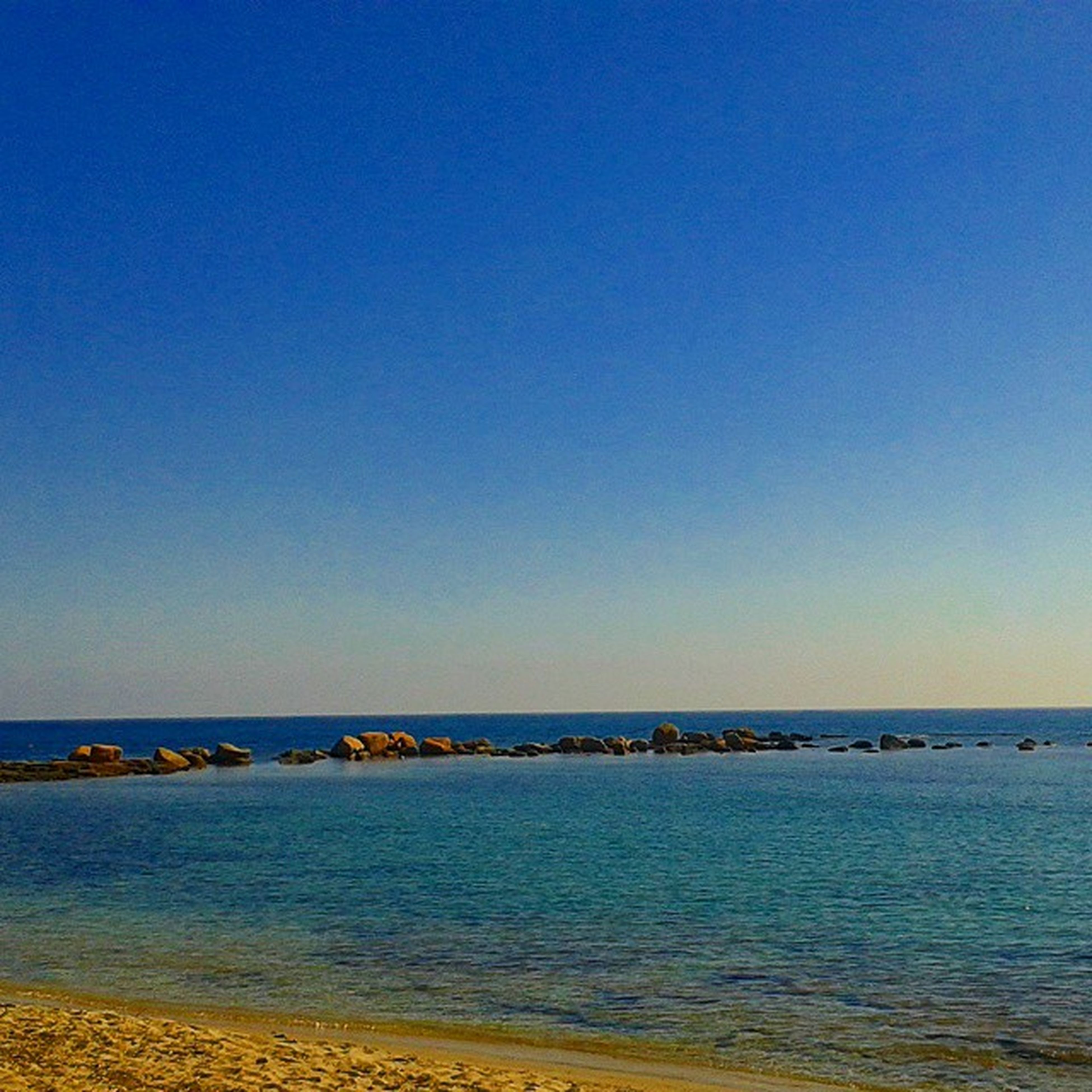 clear sky, sea, copy space, water, blue, horizon over water, tranquil scene, tranquility, beach, scenics, beauty in nature, nature, shore, idyllic, sand, calm, remote, coastline, outdoors, seascape