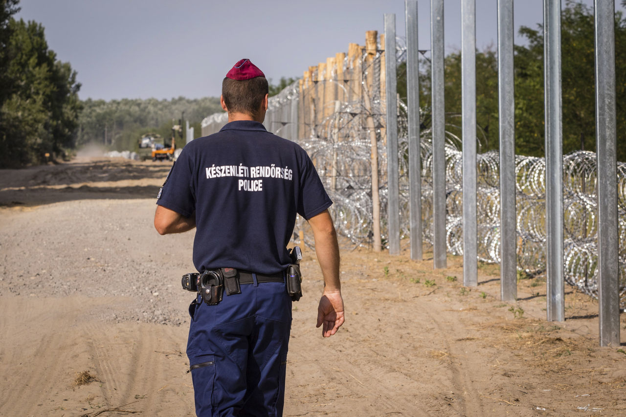 rear view, real people, uniform, text, safety, standing, protection, police force, occupation, men, casual clothing, one person, authority, law, day, police uniform, outdoors, prisoner, prison, protective workwear, sky, young adult, adult, people