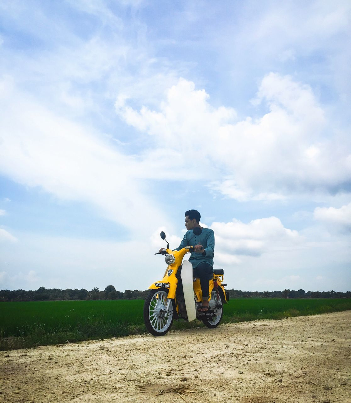 cloud - sky, transportation, field, sky, land vehicle, motorcycle, one person, mode of transport, day, men, real people, riding, landscape, outdoors, lifestyles, full length, motocross, nature, young adult, one man only, adult, people