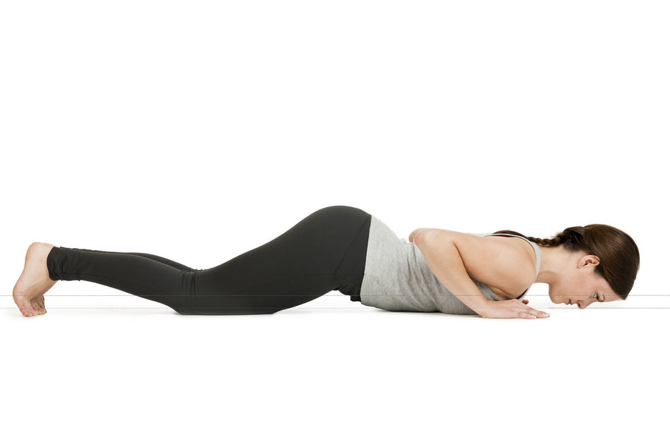 Side full body view of a young woman in front of white background showing the Yoga exercise knee chest Chin (Ashtanga namaskar). Adult Adults Only Ashtanga Ashtanga Namaskar Ashtangayoga Beauty Beauty Girl Full Body Shot Lying On The Belly Namaskar Profile View Side View Studio Shot White Background Woman Yoga Yoga Pose Yoga Position Young Woman