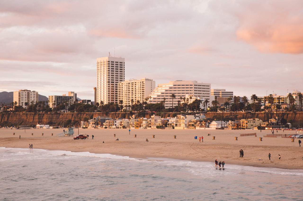 architecture, beach, building exterior, sand, built structure, sky, cloud - sky, outdoors, real people, city, nature, travel destinations, sea, large group of people, men, leisure activity, scenics, day, beauty in nature, cityscape, people