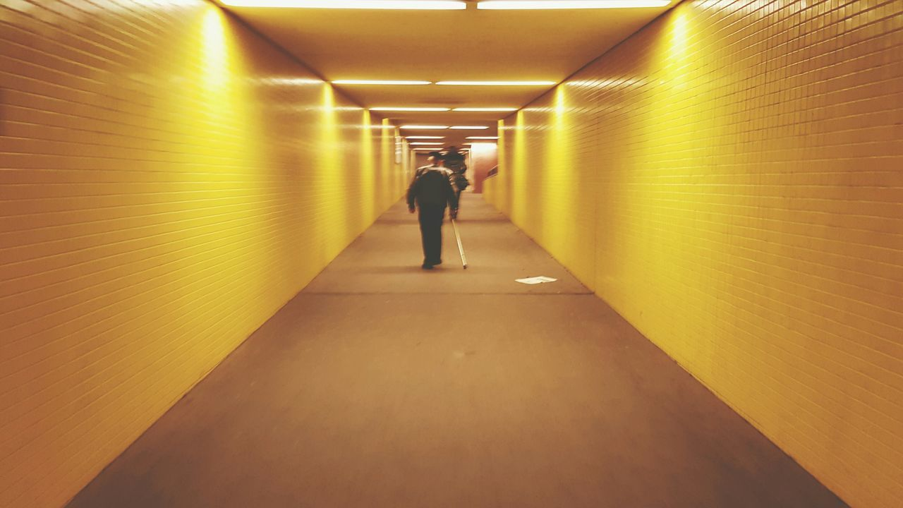 illuminated, real people, the way forward, tunnel, indoors, architecture, full length, rear view, built structure, walking, lifestyles, women, men, day, people