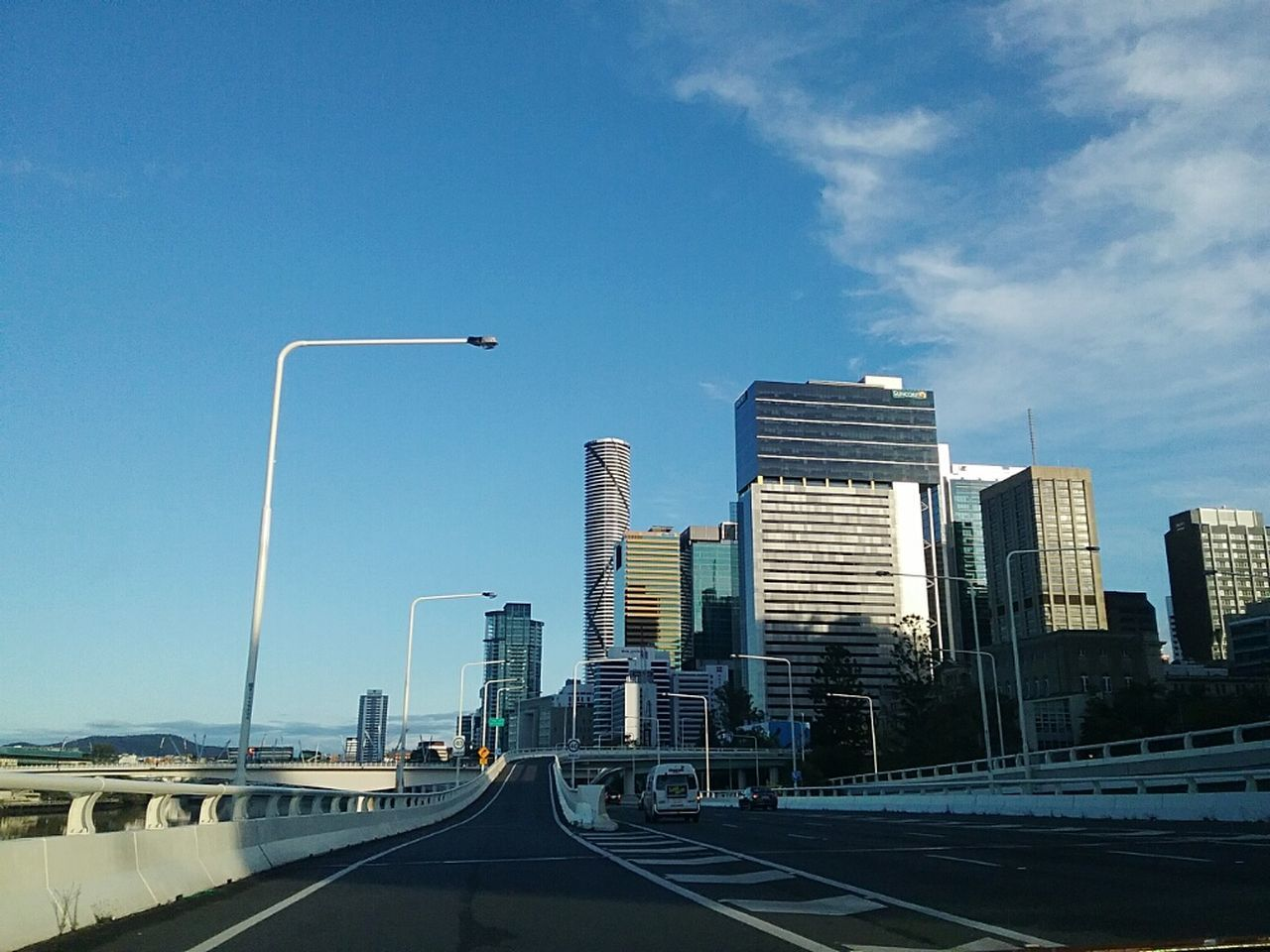 architecture, skyscraper, city, road, built structure, building exterior, transportation, the way forward, street light, modern, sky, day, city life, street, outdoors, cityscape, travel destinations, no people, road sign, clear sky, urban skyline