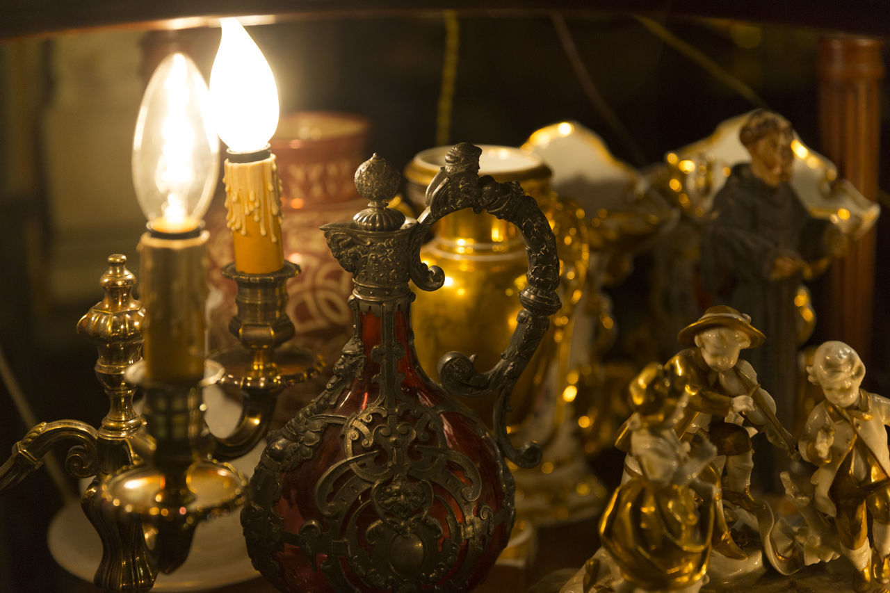 candle, illuminated, indoors, no people, gold colored, focus on foreground, flame, close-up, statue, day