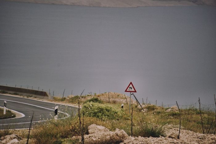Traffic Signs Slippery Roads Curved Road Mediterranean  Transportation Traveling No People Traffic Warning Sign Warning Sea Seascape Your Ticket To Europe