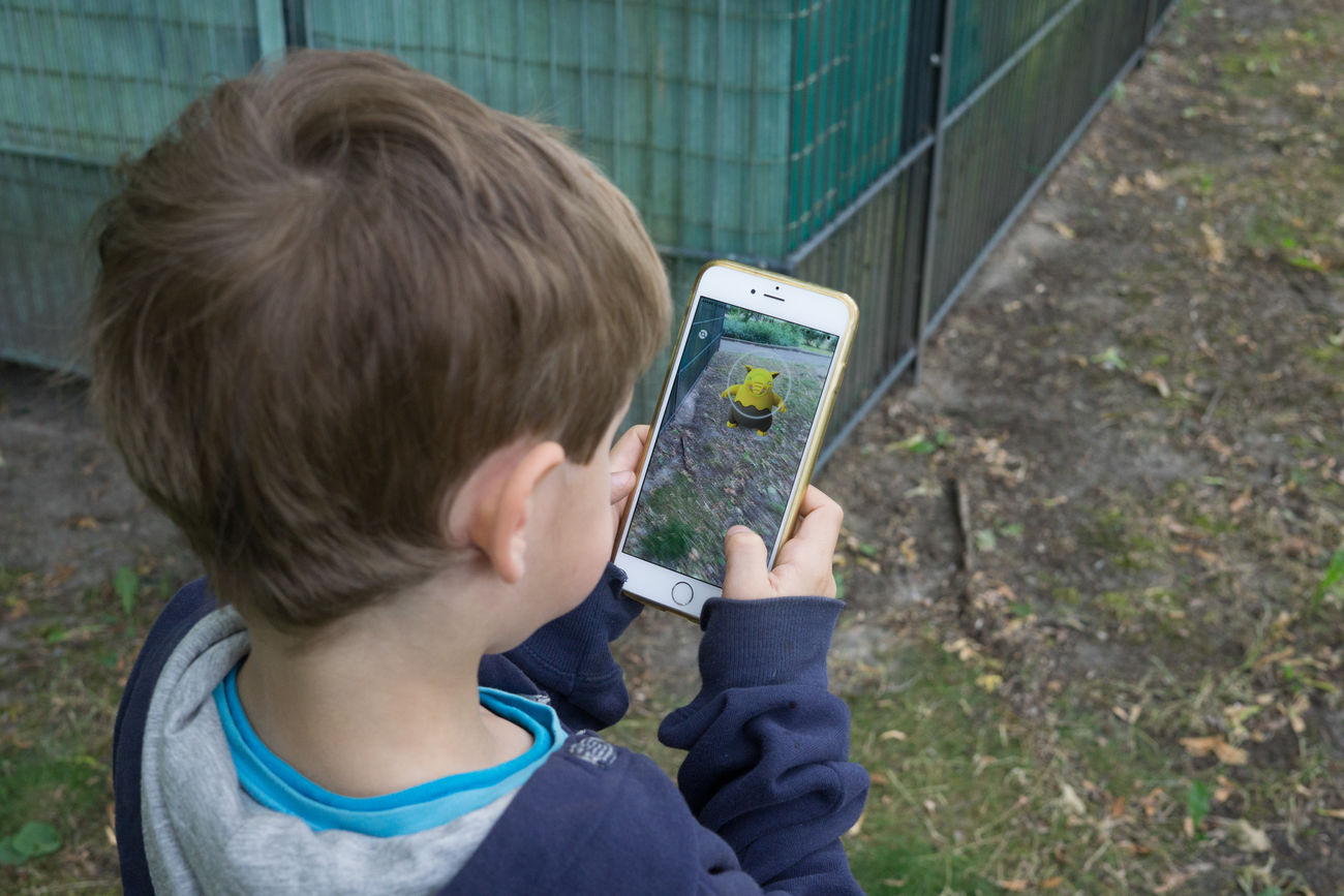 BERLIN, GERMANY - JUNE 18, 2016: Five year old boy playing Pokemon Go in Berlin, Germany as the augmented reality app was released by Nintendo for the German market. App Augmented Reality Boy Catching Child Connectivity Game Hunting Internet IPhone Kids Nintendo Online  People Person Playing Pokemon Go Pokémon Screen Smartphone