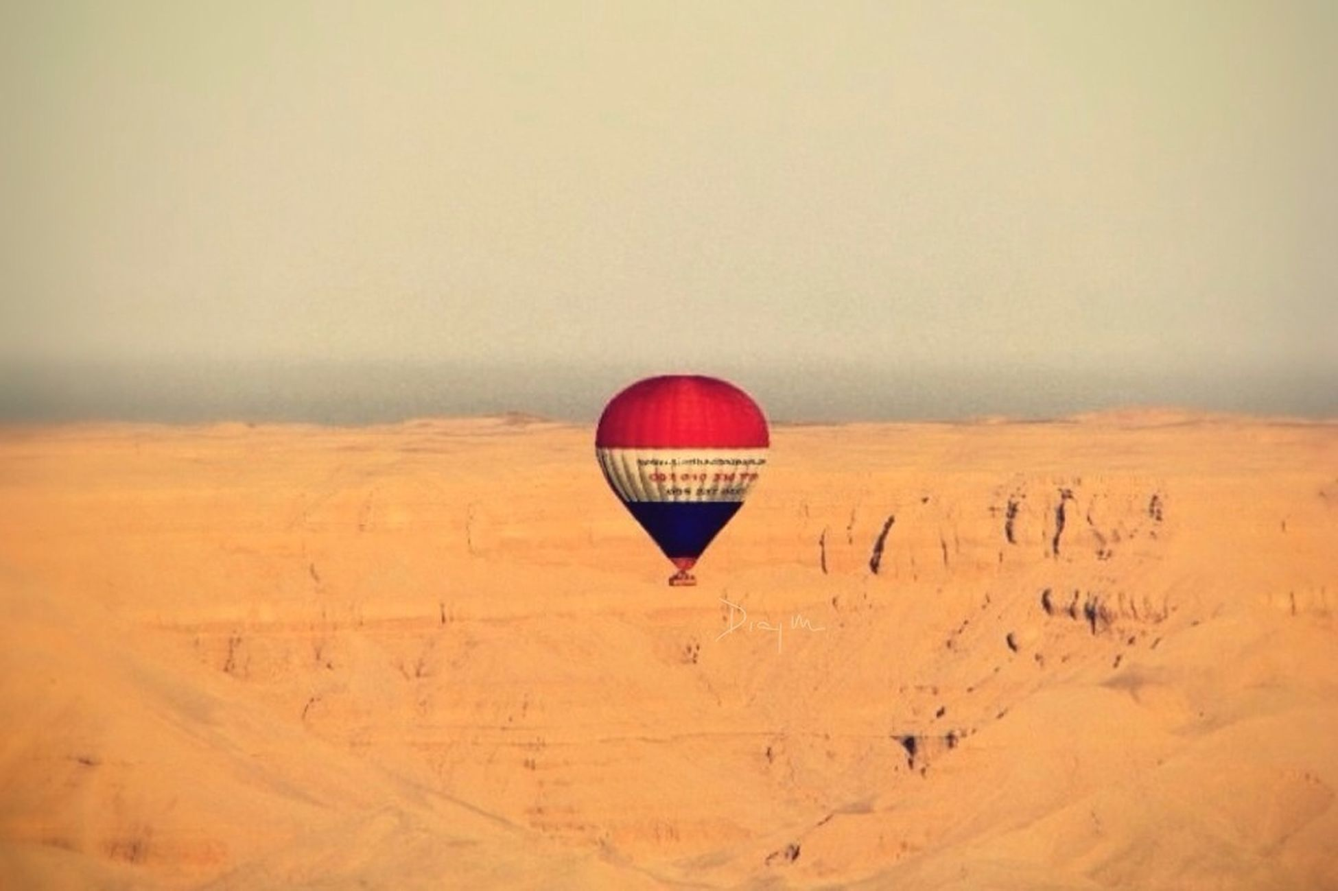 sand, landscape, red, tranquility, beach, tranquil scene, copy space, desert, clear sky, scenics, sky, nature, hot air balloon, arid climate, remote, horizon over land, non-urban scene, beauty in nature, parachute, outdoors