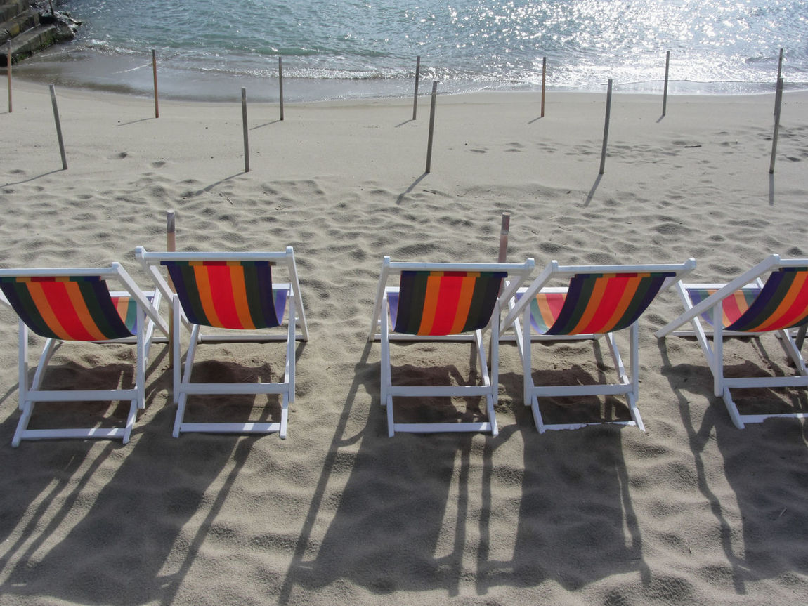 Row of colorful wooden chairs at Marina di Pisa sand beach . Tuscany, Italy Beach Chair Coast Colorful Day Destination In A Row Italy Marina Di Pisa Marine Relax Sand Seashore Seaside Season  Shiny Shore Summer Sunlight Sunny Tide Tuscany Water Weather Wooden