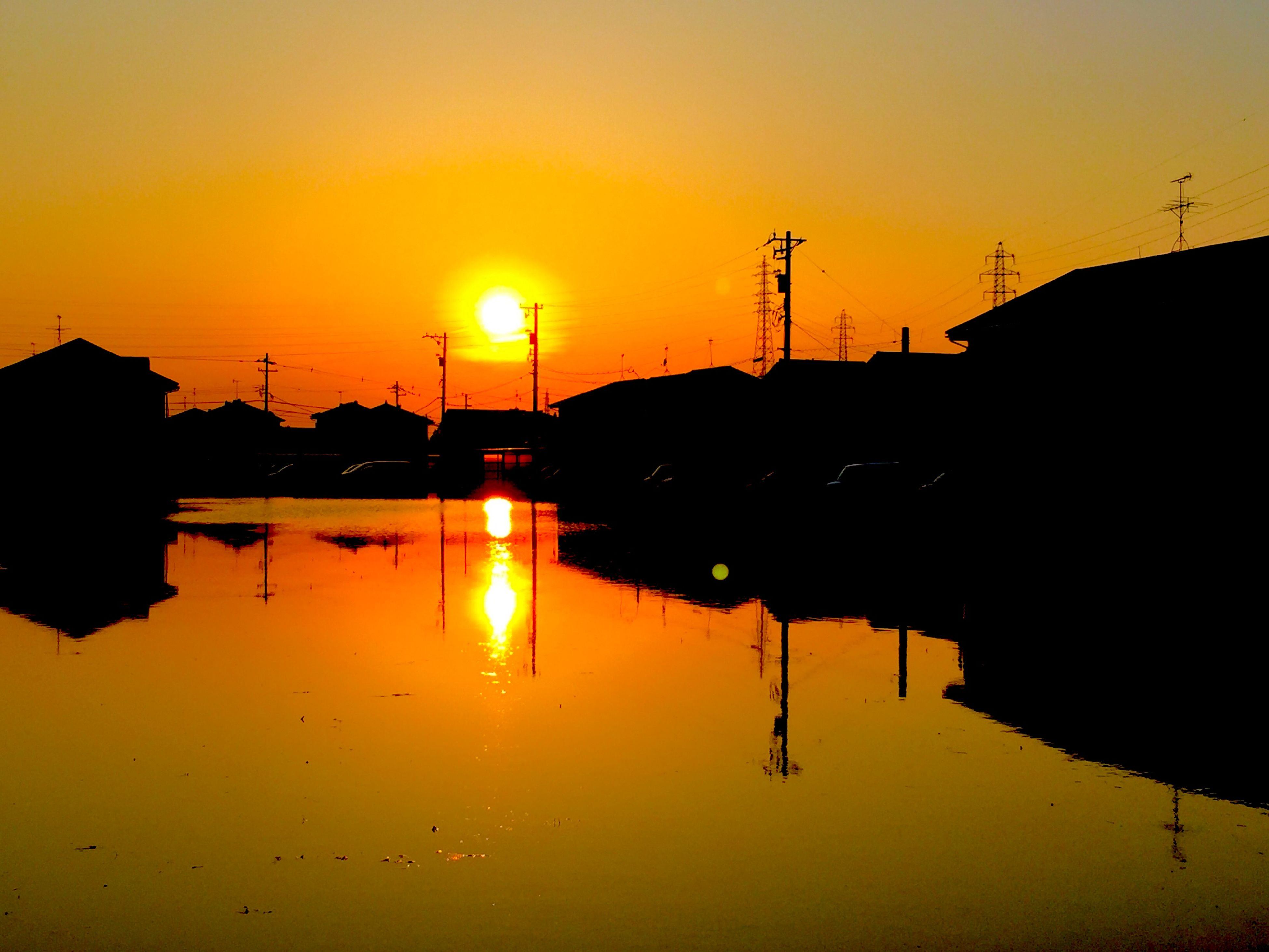 water, sunset, reflection, silhouette, calm, waterfront, tranquil scene, scenics, orange color, tranquility, lake, standing water, sun, idyllic, beauty in nature, symmetry, nature, remote, cloud, atmospheric mood, majestic, solitude, outline, sky, vibrant color, water surface, no people, reflected, bridge, sea