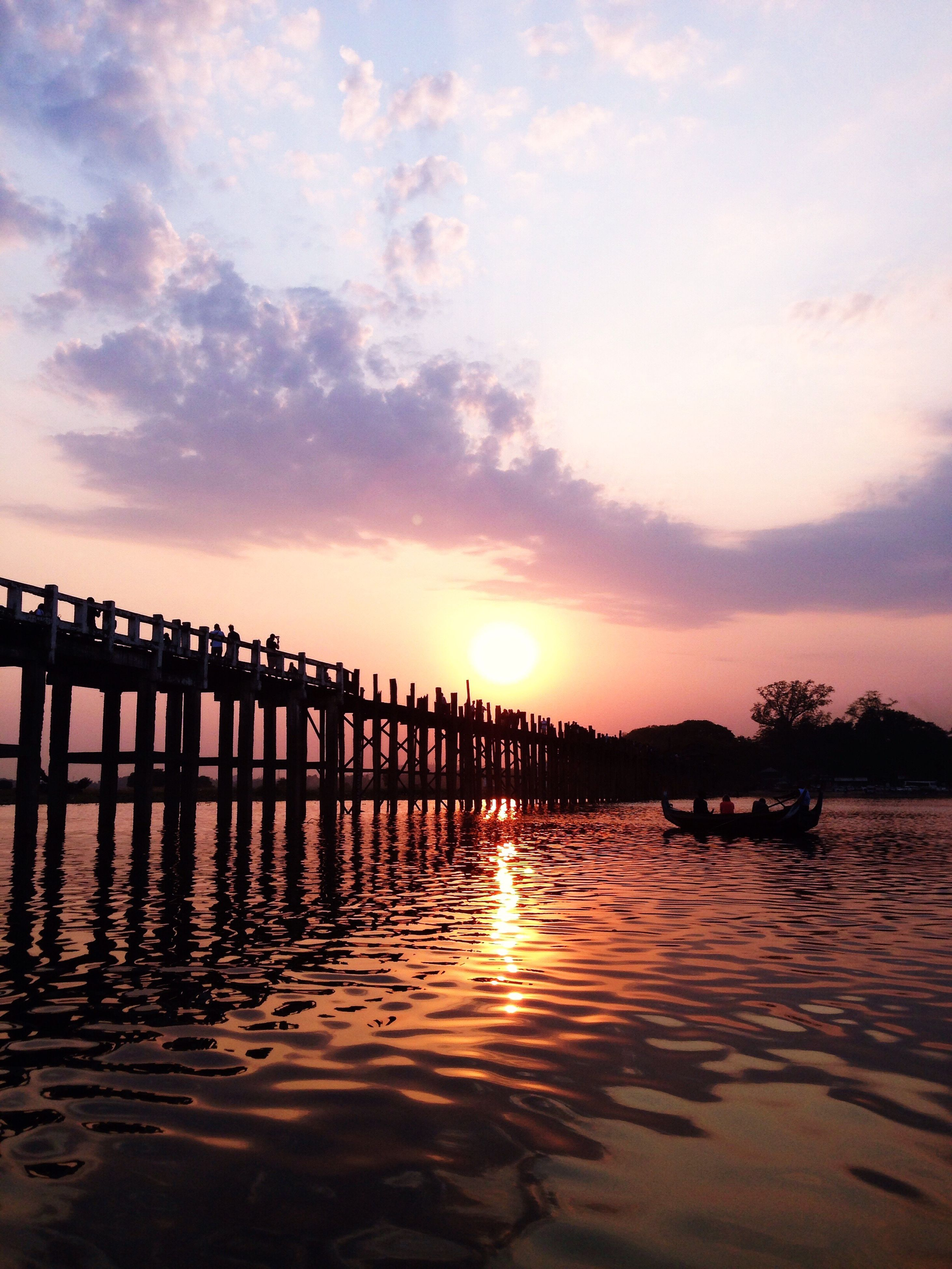 water, sunset, reflection, sky, tranquil scene, tranquility, pier, scenics, beauty in nature, sun, nature, cloud - sky, idyllic, outdoors, cloud, orange color, no people, non-urban scene, wooden post, rippled, calm, cloudy, remote, sunbeam