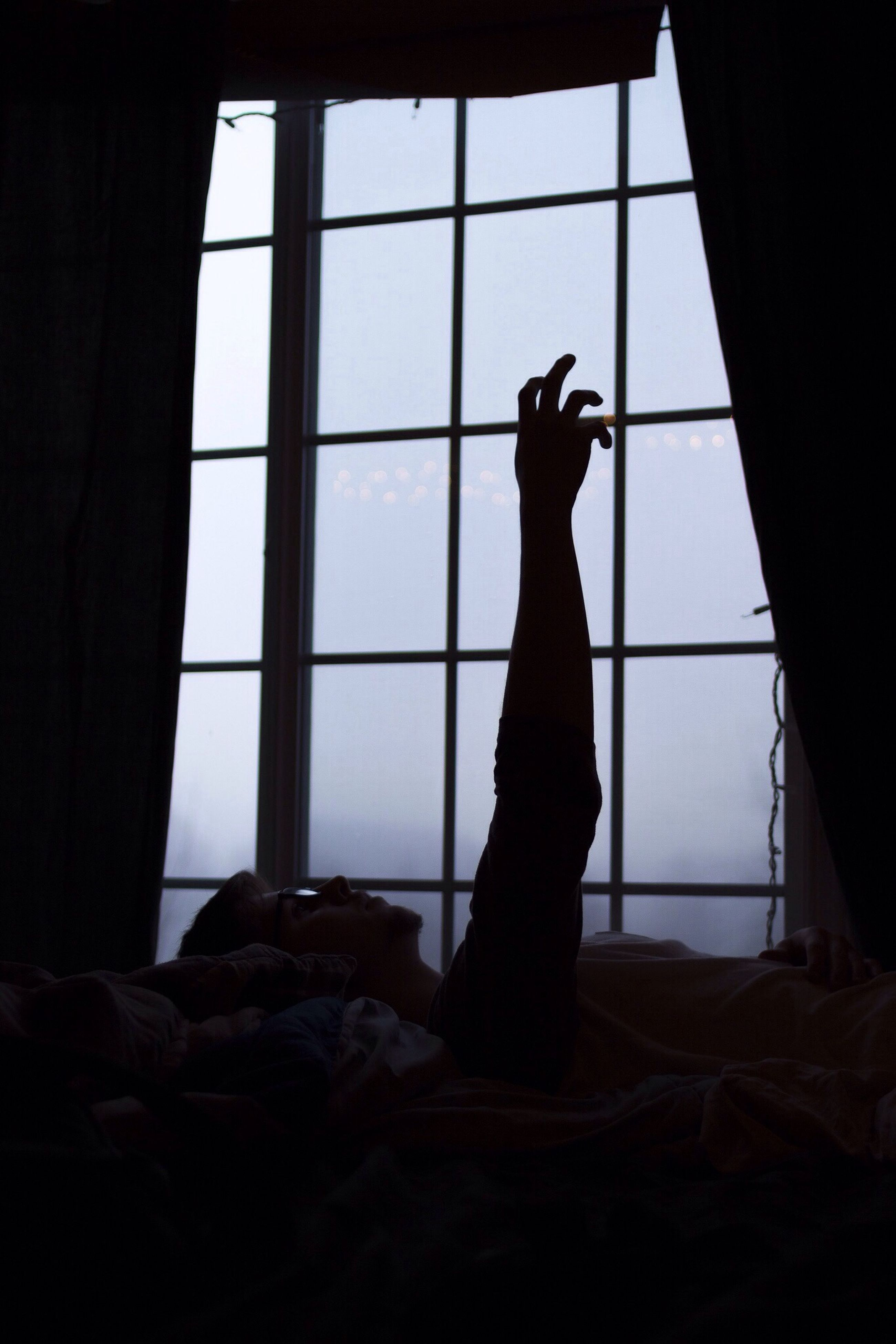 indoors, window, silhouette, sitting, relaxation, home interior, glass - material, transparent, lifestyles, looking through window, standing, person, men, curtain, day, sunlight, leisure activity, low section