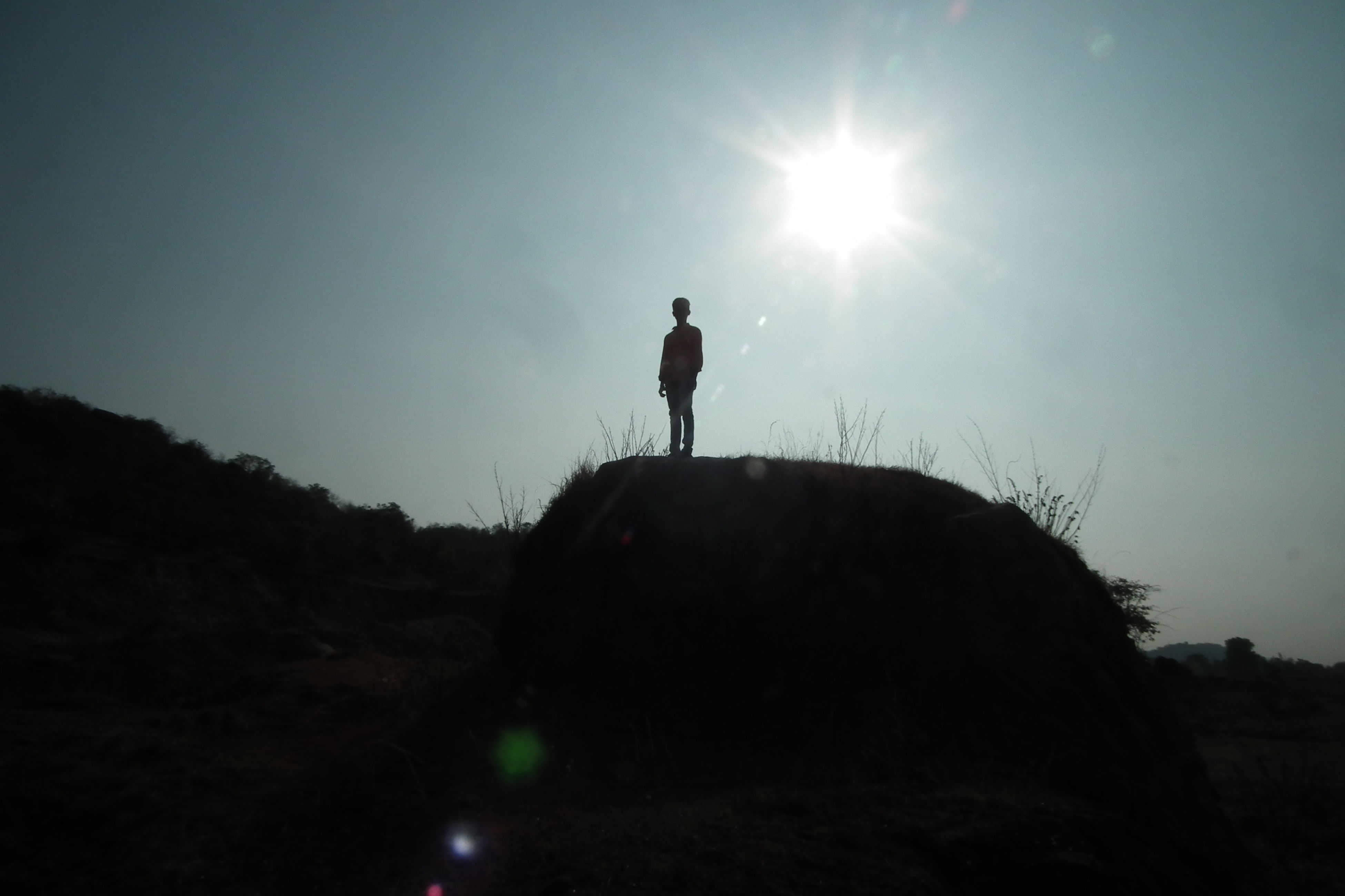 leisure activity, silhouette, real people, sun, standing, one person, full length, lifestyles, nature, outdoors, sky, mountain, day, beauty in nature, people, adult