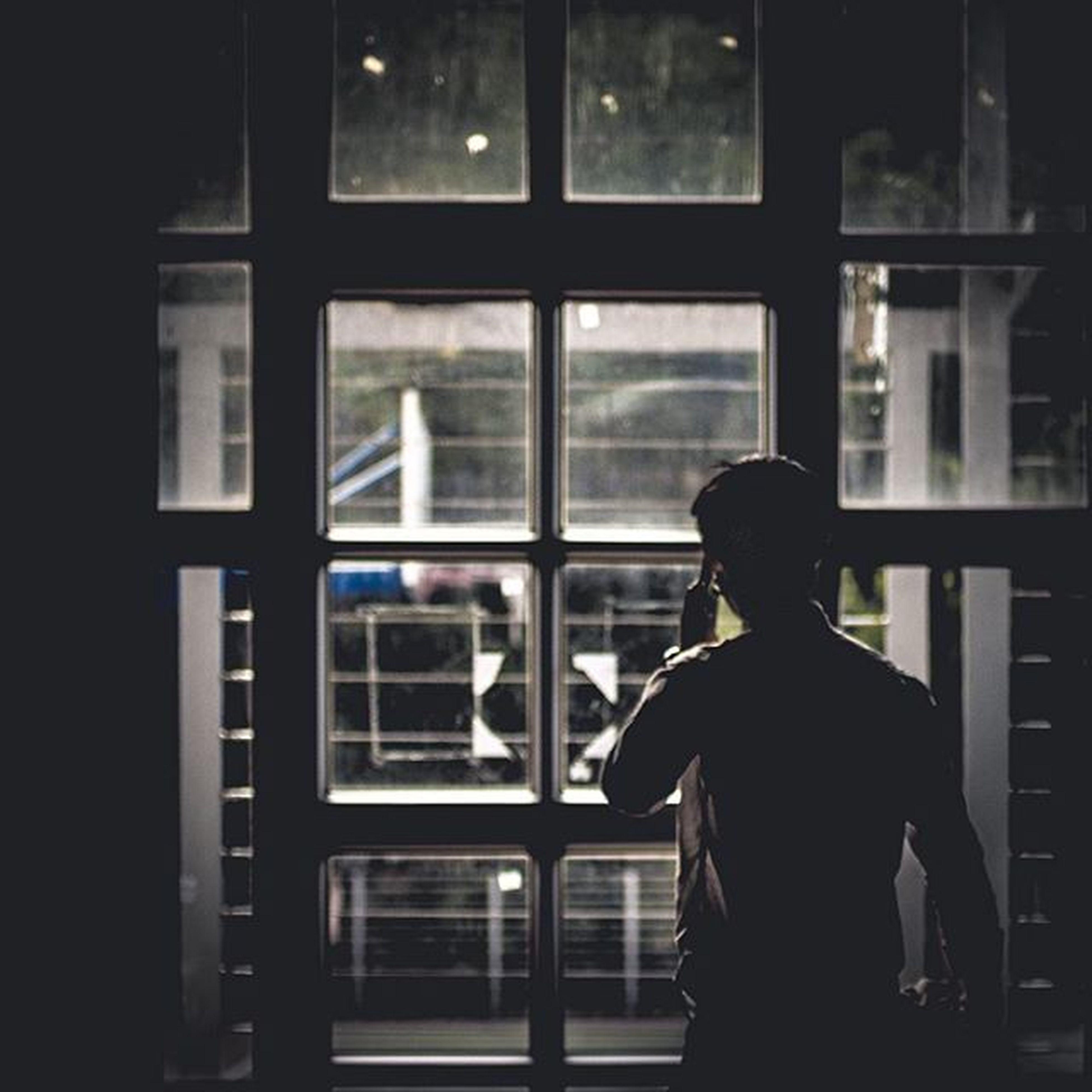 indoors, window, men, rear view, glass - material, lifestyles, standing, transparent, leisure activity, person, silhouette, built structure, architecture, three quarter length, looking through window, waist up, side view, sitting