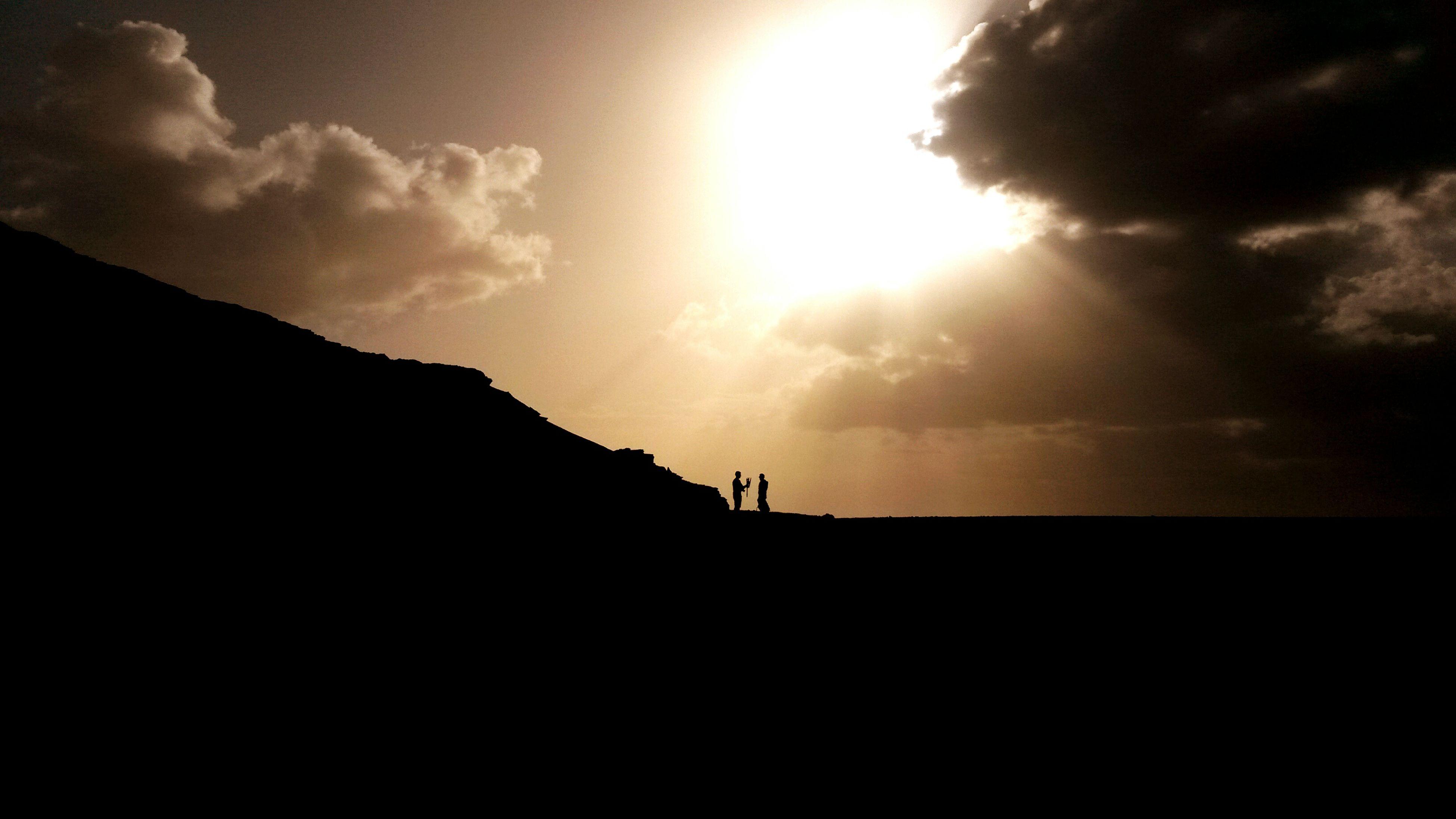 sun, silhouette, sunbeam, sky, sunlight, mountain, scenics, tranquil scene, tranquility, beauty in nature, lens flare, cloud - sky, nature, cloud, sea, idyllic, sunset, mountain range, bright, outdoors