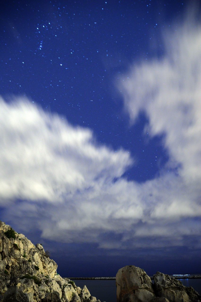 sky, scenics, nature, cloud - sky, beauty in nature, tranquility, tranquil scene, sea, rock - object, no people, horizon over water, outdoors, star - space, low angle view, awe, night, blue, astronomy, water, space, galaxy