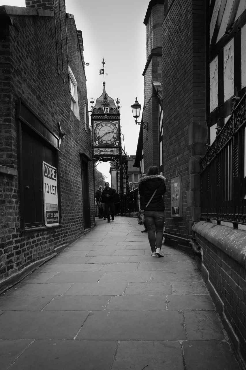 architecture, built structure, building exterior, walking, real people, text, full length, the way forward, rear view, men, city, day, outdoors, one person, mammal, sky, people