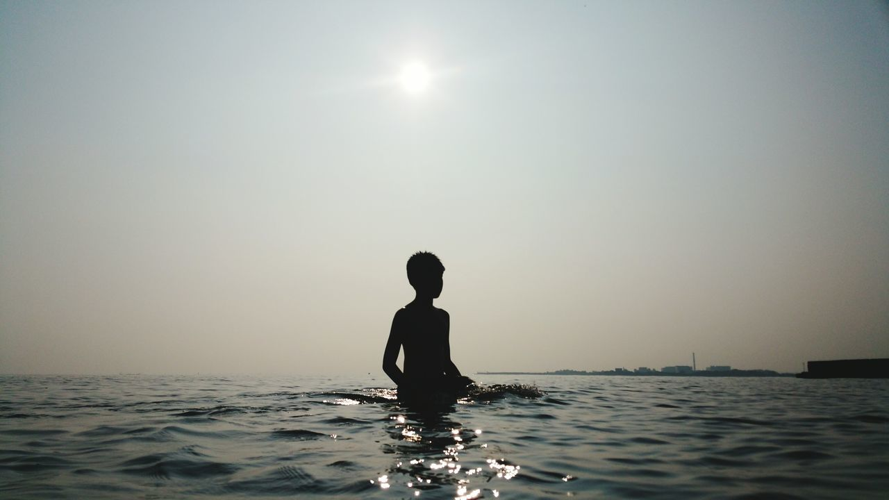 Silhouette Boy Standing In Sea Against Clear Sky