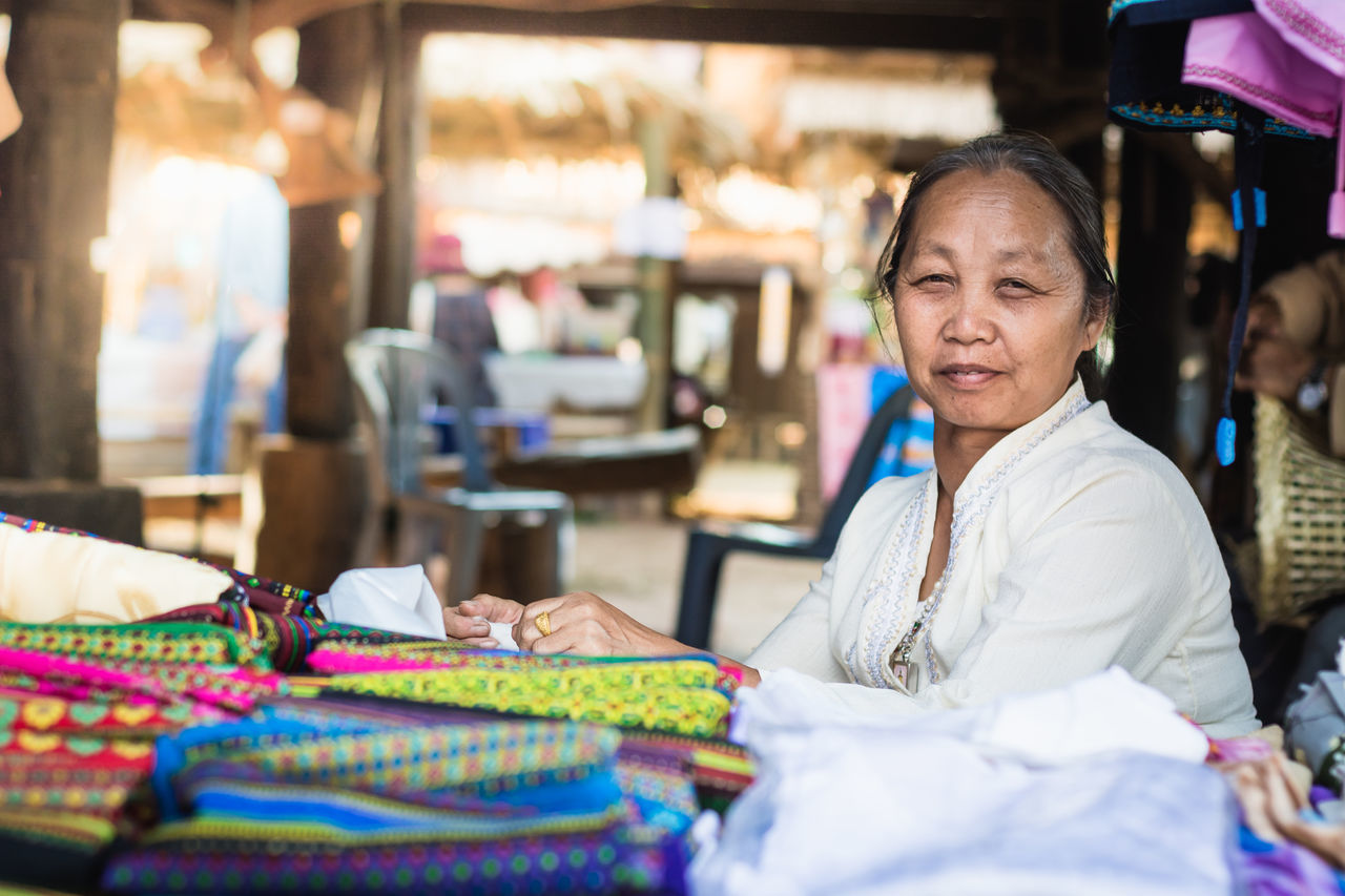 small business, retail, market, store, for sale, market stall, textile, fashion, textile industry, real people, choice, one person, focus on foreground, scarf, business, multi colored, women, day, wool, outdoors, people