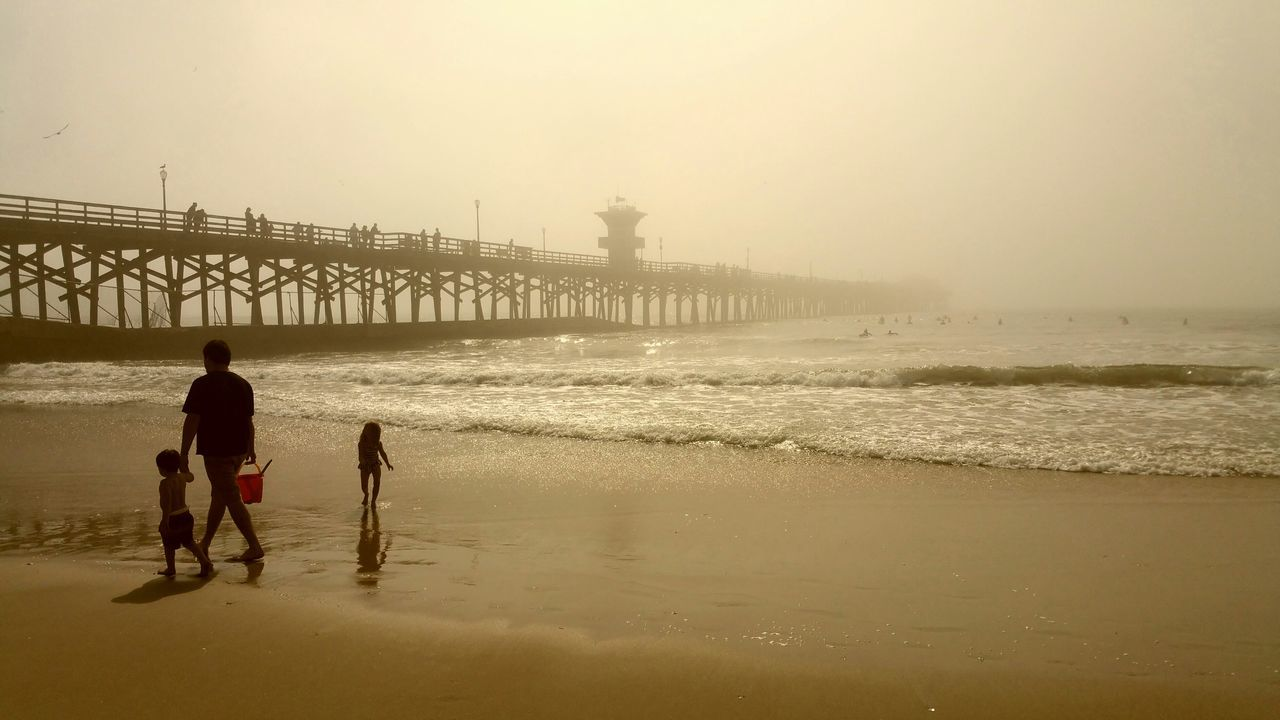Ready To Have Fun Enjoying Life Playing Ocean Foggy Day Sand People Having Fun Dad And Children At The Beach Natural Beauty Golden Pier Fading Into Mist White Space Boy girl Family Showcase: February Seal Beach California Surf's Up Surfer Waiting For Waves Surfing Paradise