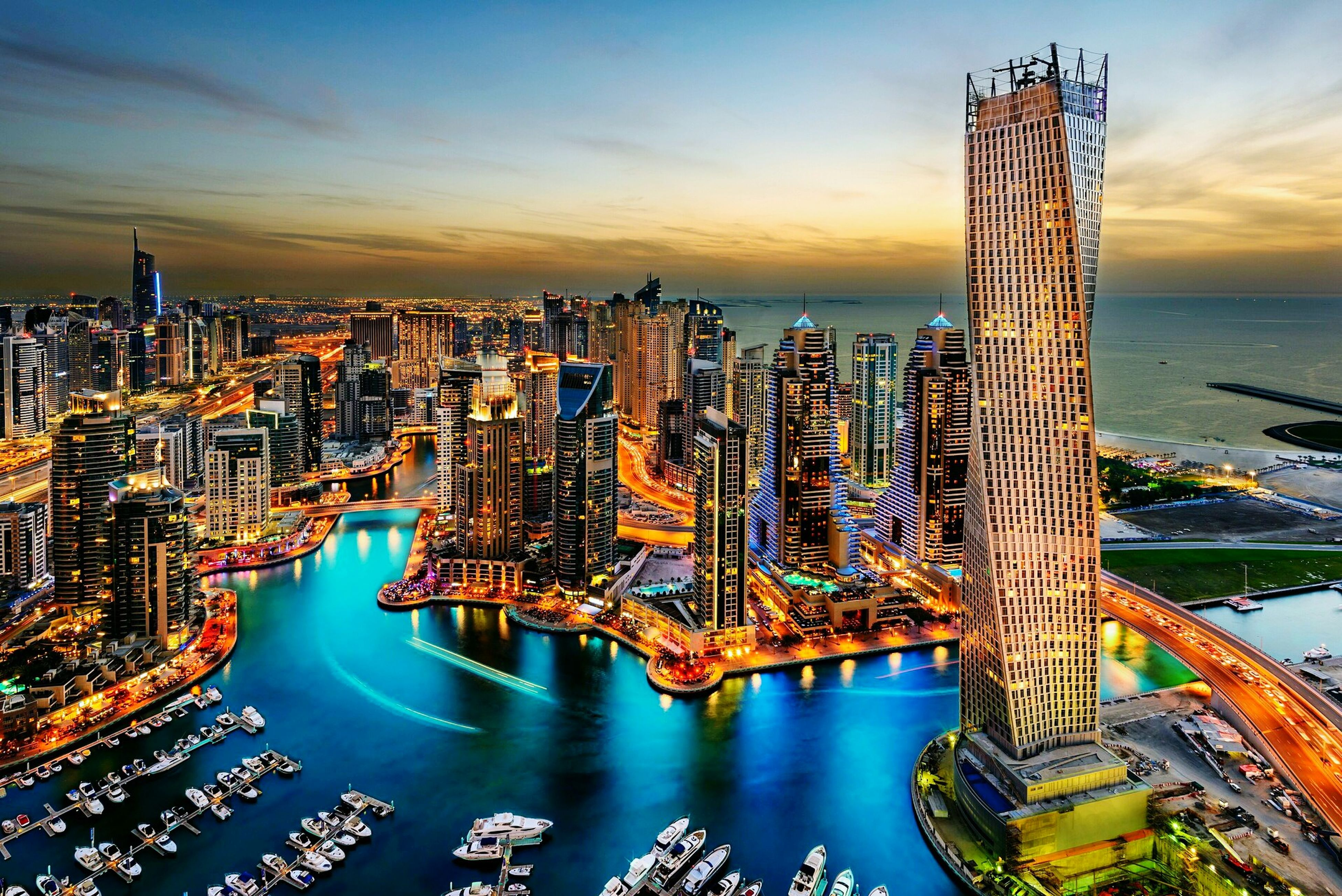 architecture, building exterior, skyscraper, water, built structure, sky, high angle view, travel destinations, waterfront, no people, cityscape, outdoors, city, illuminated, sunset, night, nature, modern, nautical vessel, urban skyline
