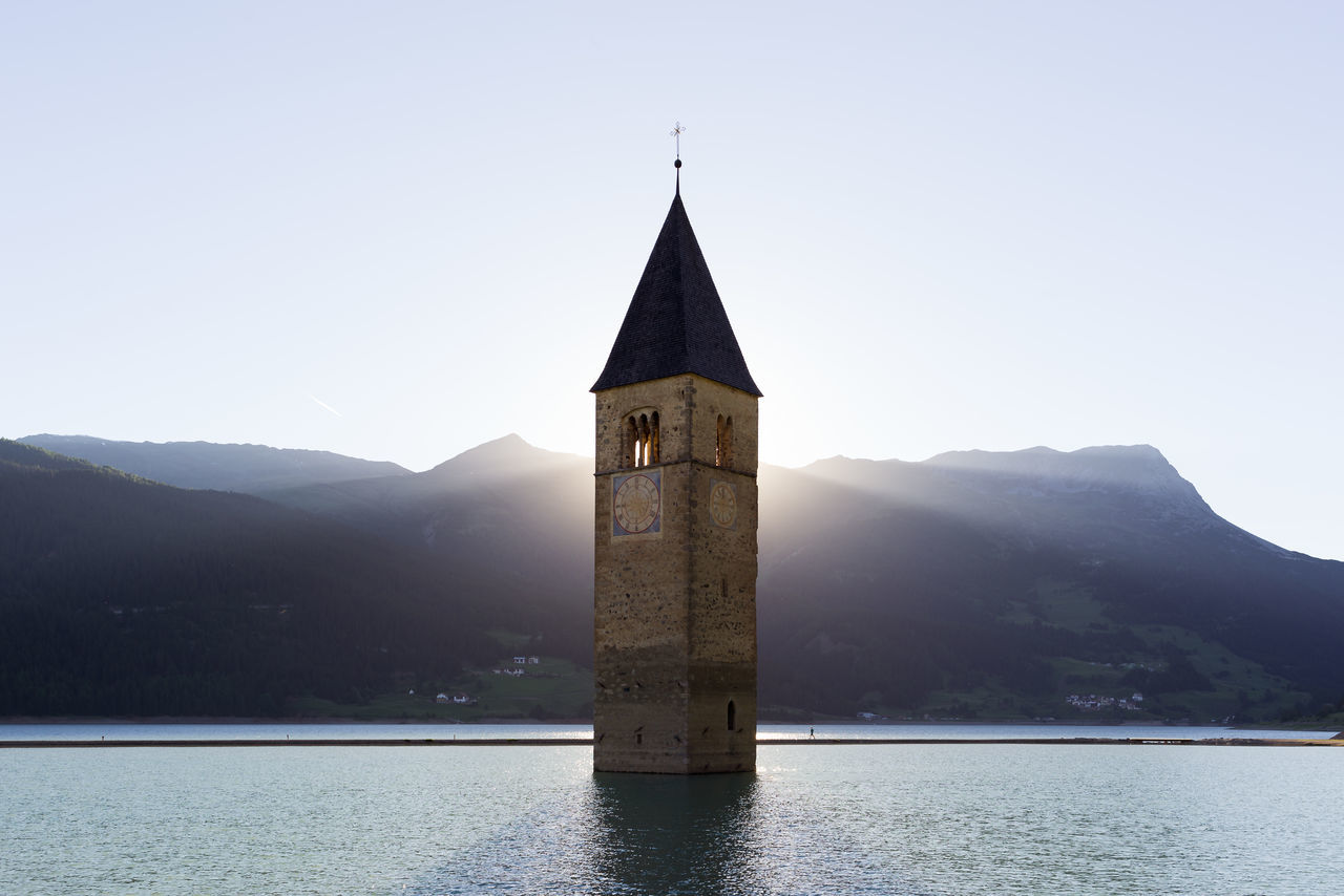 Scenic bell tower with backlit rays of sun submerged in Resia water lake in Alto Adige Alto Adige Architecture Austria Church Morning Travel alps bell tower building clock tower europe evening italy lake landmark memory mist mountains old buildings religion scenics sunrise sunset switzerland water Fresh on Market 2017