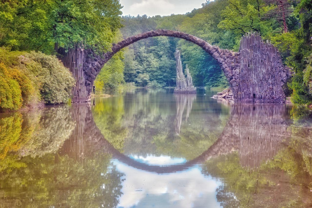 """Die Rakotzbrücke, im Volksmund auch Teufelsbrücke genannt. Auch wenn selbst das Schild direkt an der Brücke die Bezeichnung Rackotzbrücke trägt, hat sich überwiegend die Schreibweise ohne """"c"""" durchgesetzt. Die imposante Bogenbrücke wurde um 1860 in zehnjähriger Bauzeit von Friedrich Hermann Rötschke im Zuge der Parkbebauung aus Basalt- und Feldsteinen errichtet und überspannt den 35 m breiten Rakotzsee. Beauty In Nature Bridge - Man Made Structure Day EyeEm Best Shots EyeEm Nature Lover Gablenzbrücke Growth Idyllic Nature No People Non-urban Scene OpenEdit Outdoors Rakotzbridge Reflection Scenics Standing Water Tranquil Scene Tranquility Tree Water"""