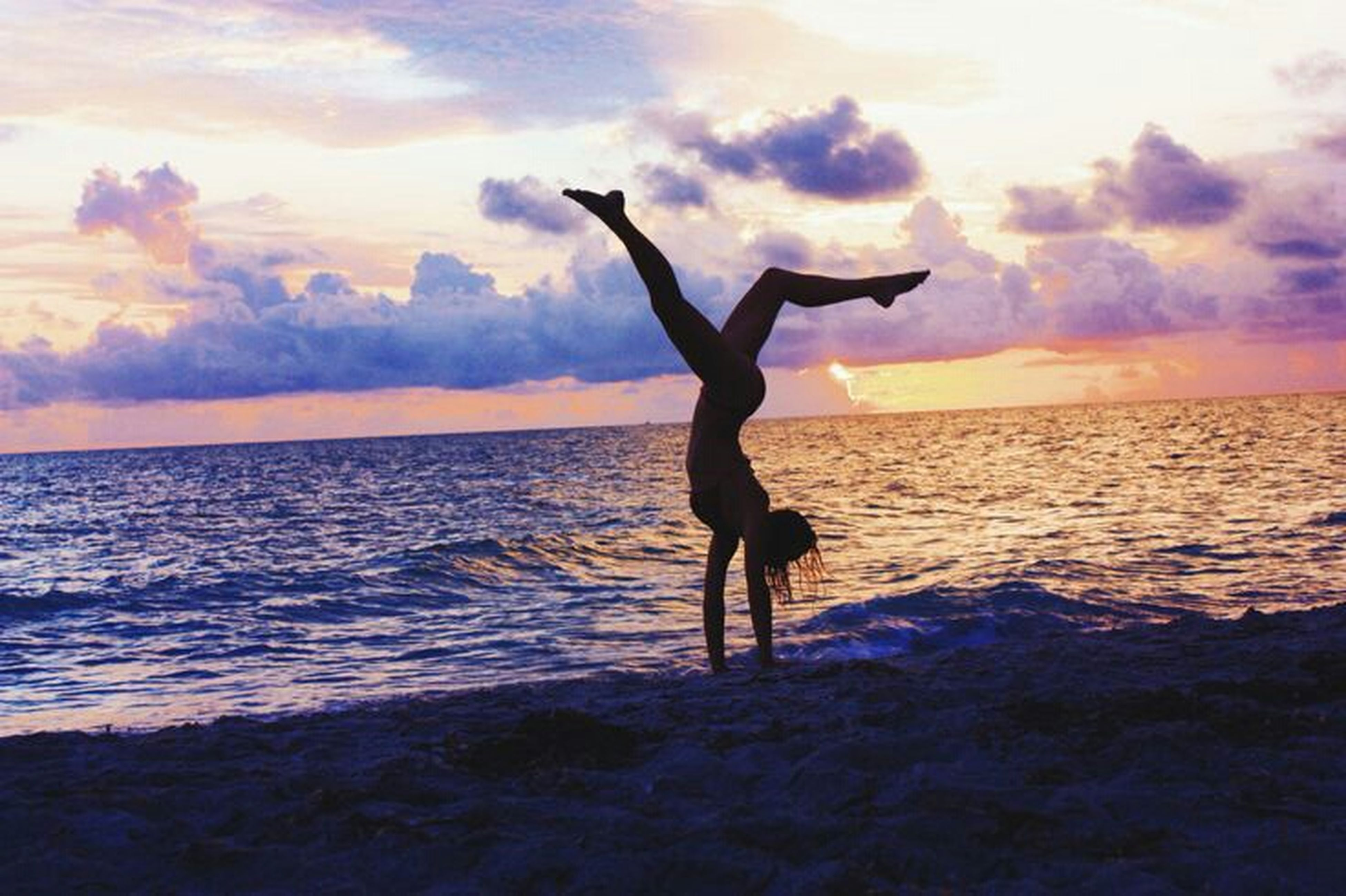 sea, water, sky, horizon over water, sunset, full length, lifestyles, leisure activity, silhouette, scenics, cloud - sky, beach, tranquil scene, beauty in nature, arms outstretched, shore, jumping, standing