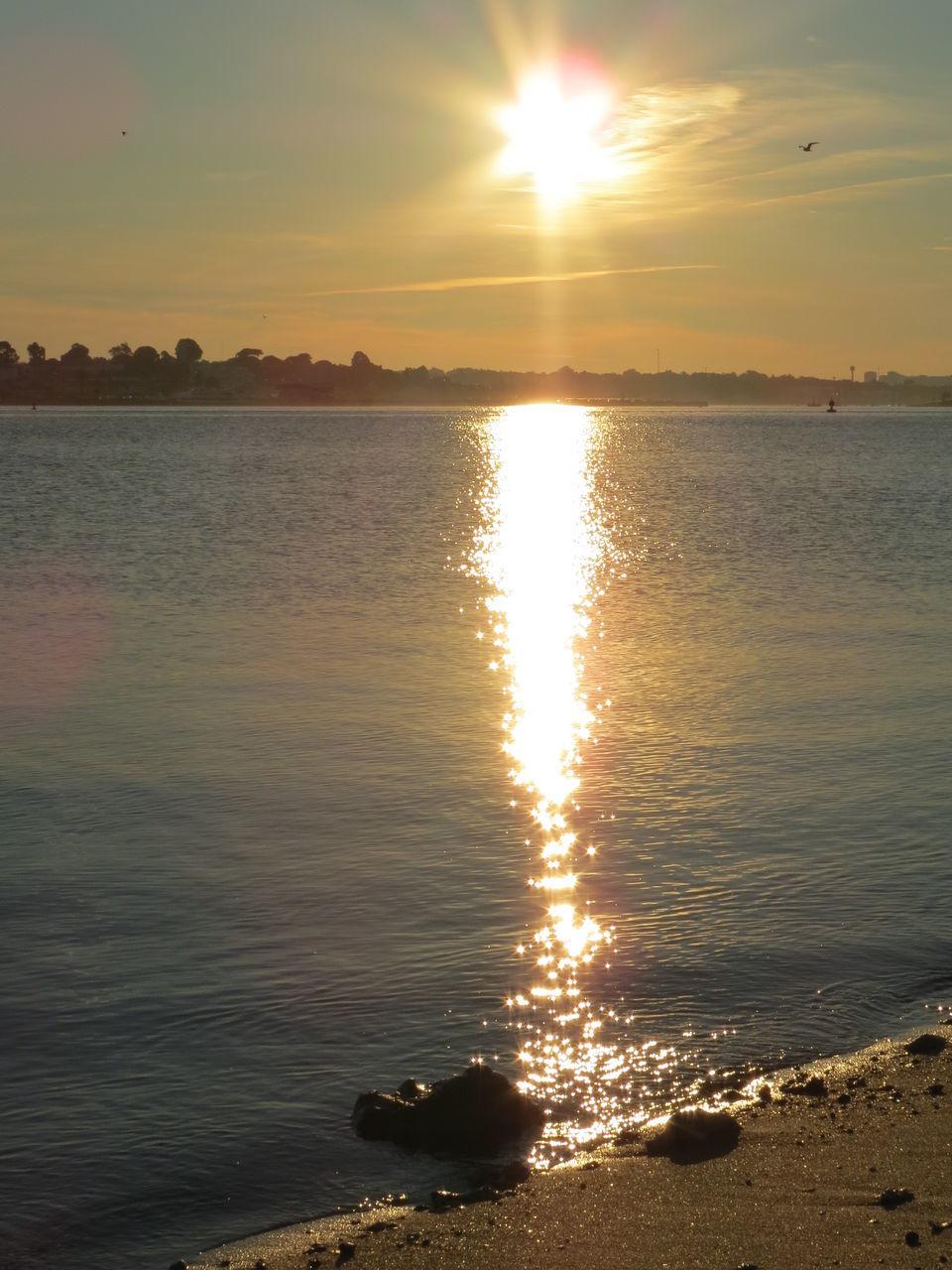 sunset, sun, beauty in nature, nature, scenics, water, sunlight, orange color, tranquility, reflection, tranquil scene, sea, sunbeam, silhouette, sky, no people, idyllic, outdoors, beach, tree