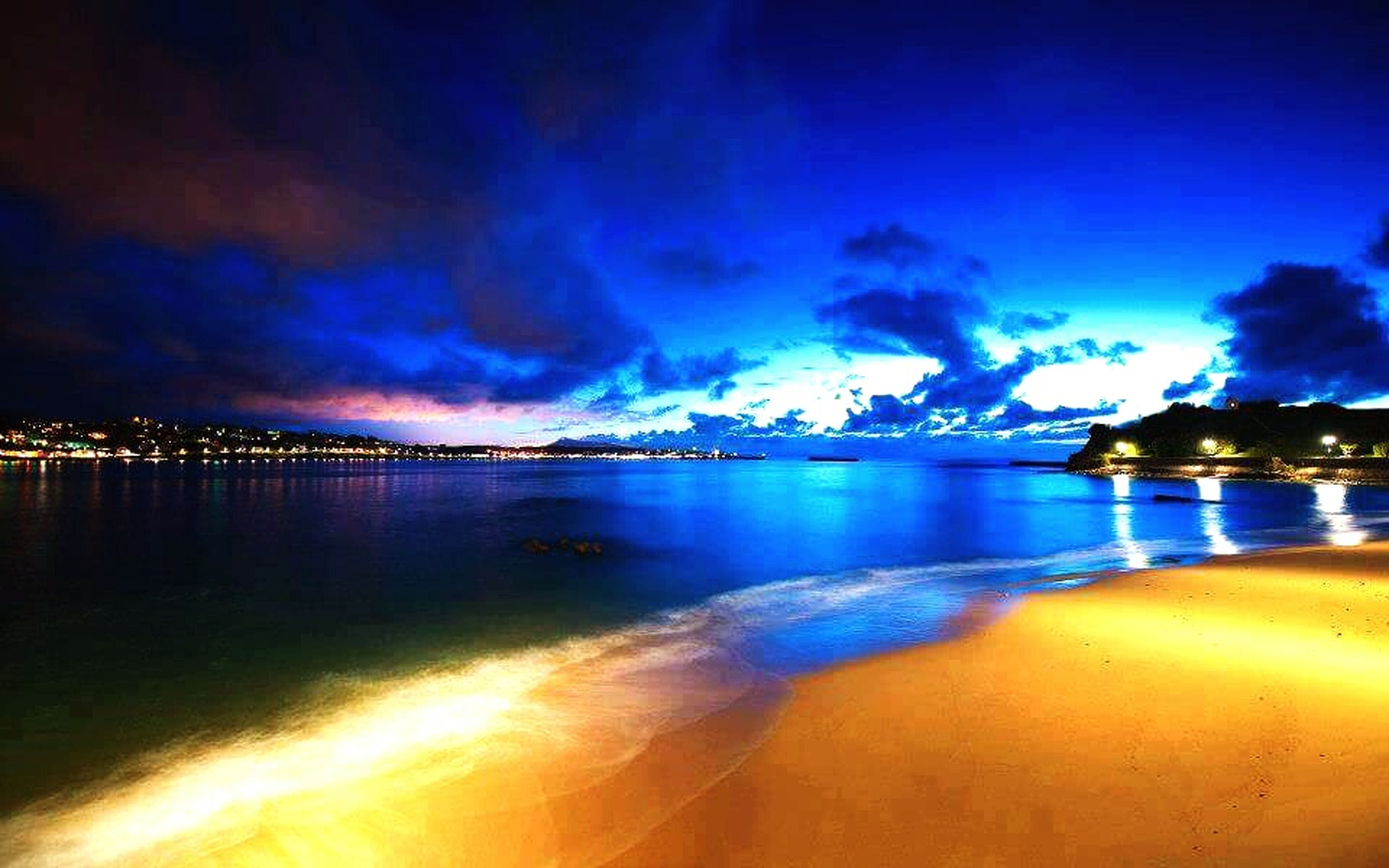 blue, illuminated, water, sky, tranquil scene, scenics, reflection, tranquility, city, sea, cloud - sky, cloud, beauty in nature, calm, nature, dramatic sky, no people, shore, blue color