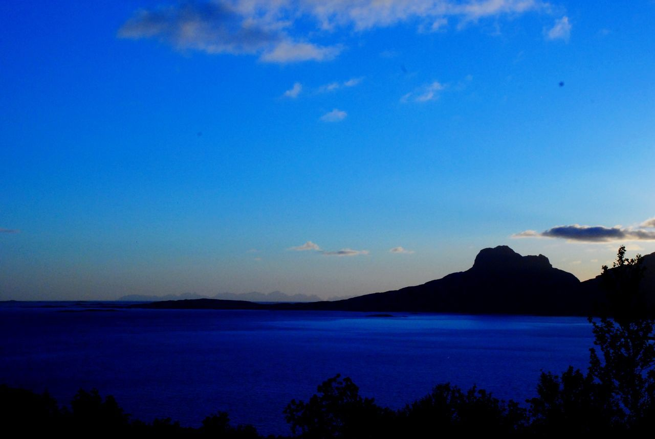 blue, beauty in nature, sky, nature, scenics, tranquil scene, tranquility, water, sea, outdoors, no people, silhouette, tree, mountain, horizon over water, day