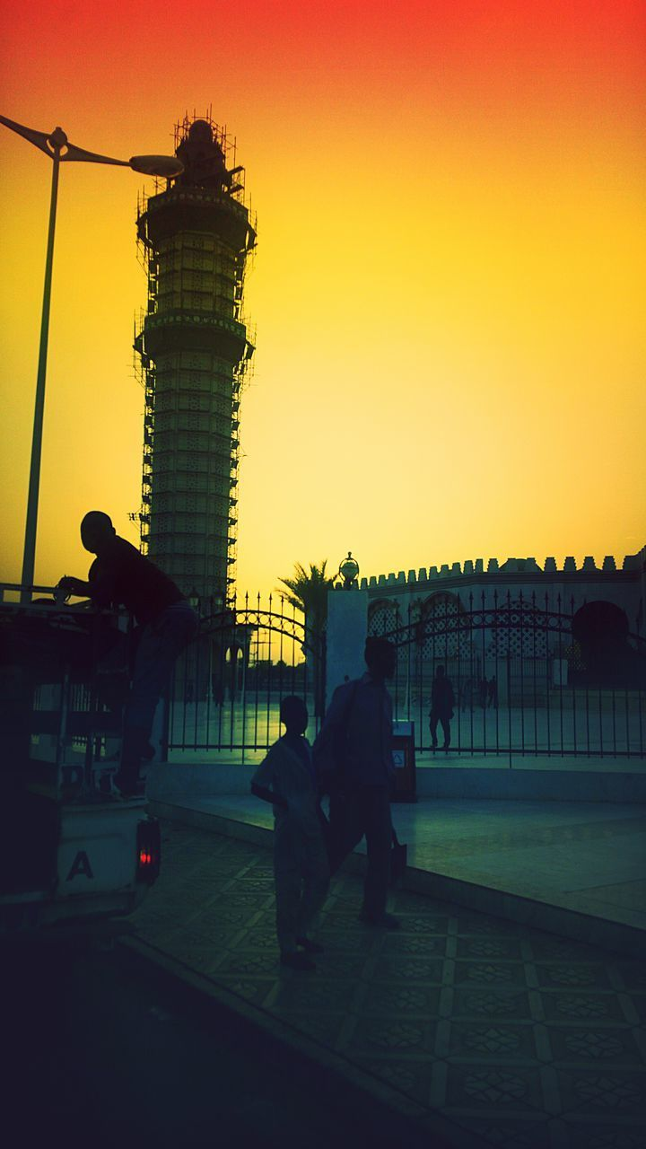 sunset, silhouette, real people, sky, outdoors, men, architecture, sitting, two people, built structure, togetherness, full length, clear sky, nature, day, people