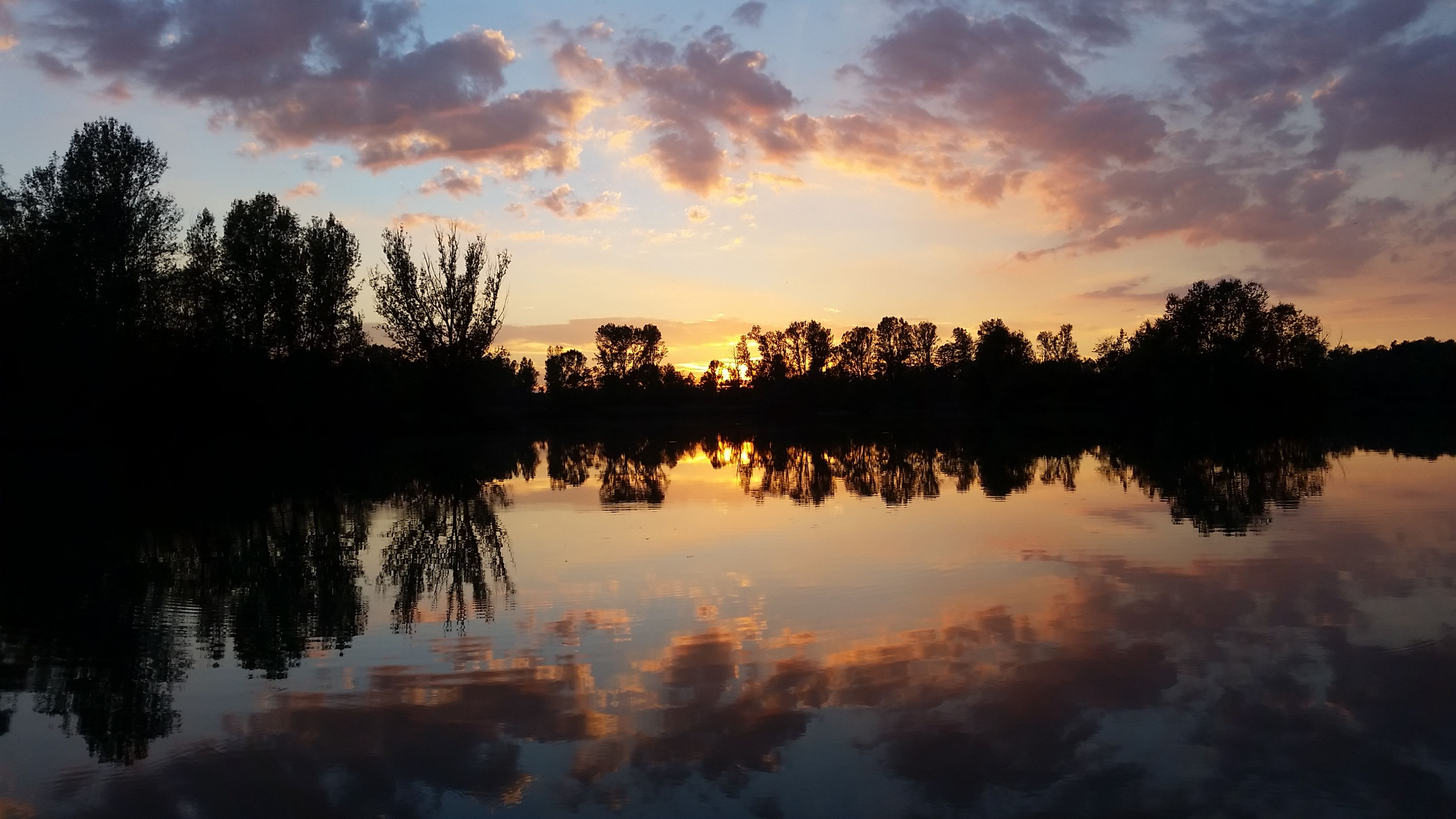 reflection, sunset, water, lake, tree, tranquil scene, scenics, tranquility, silhouette, beauty in nature, majestic, calm, waterfront, orange color, nature, sky, standing water, cloud, non-urban scene, outdoors, blue, cloud - sky, countryside, no people, outline, dramatic sky