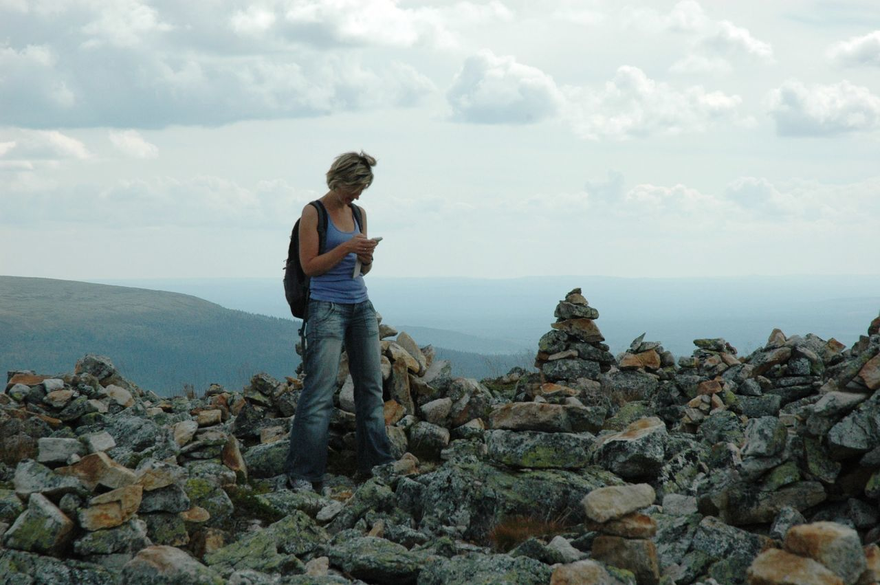 Woman Using Mobile Phone While Standing On Mountain Against Sky