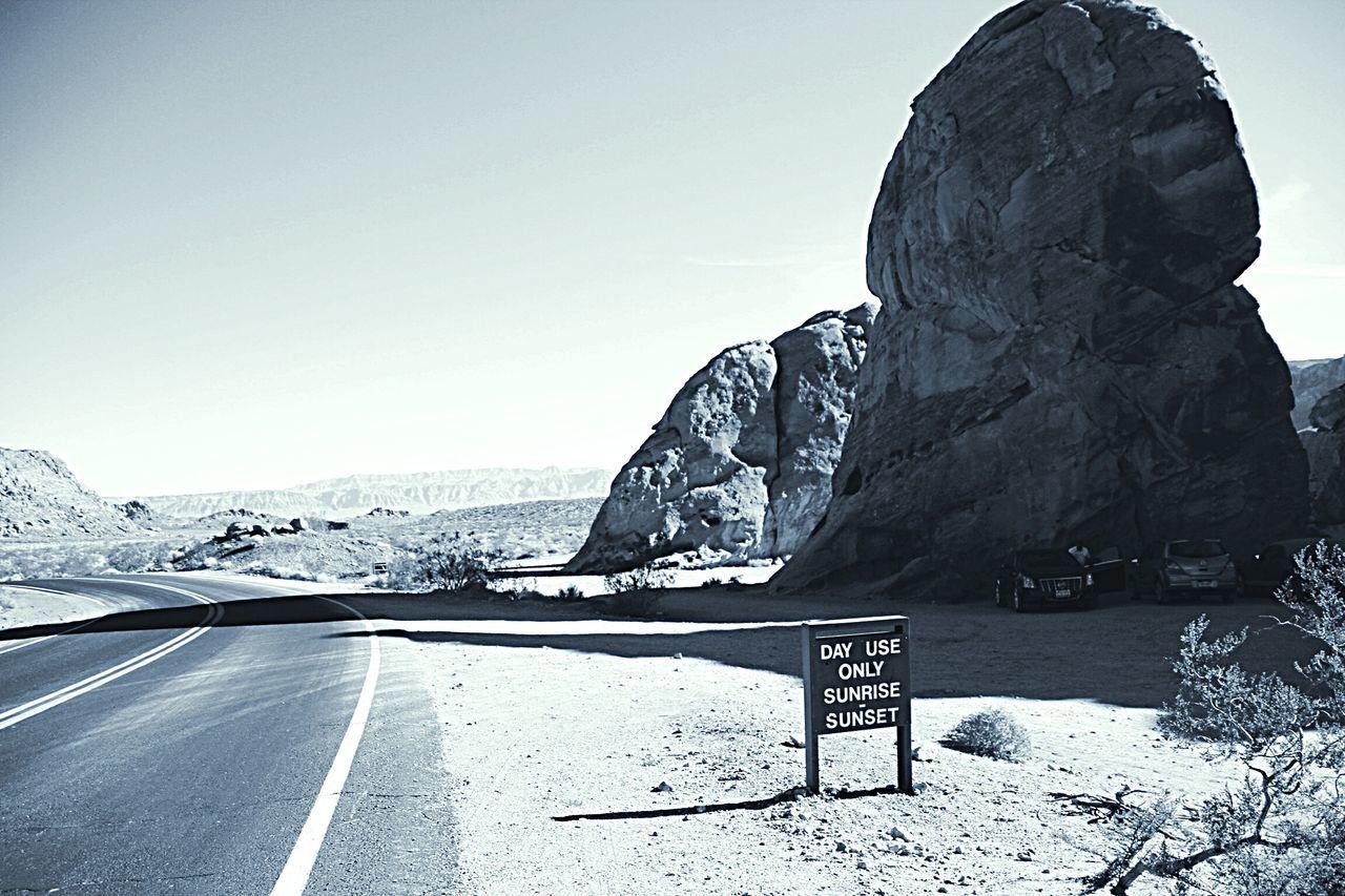 Empty Road By Rock Formations On Field