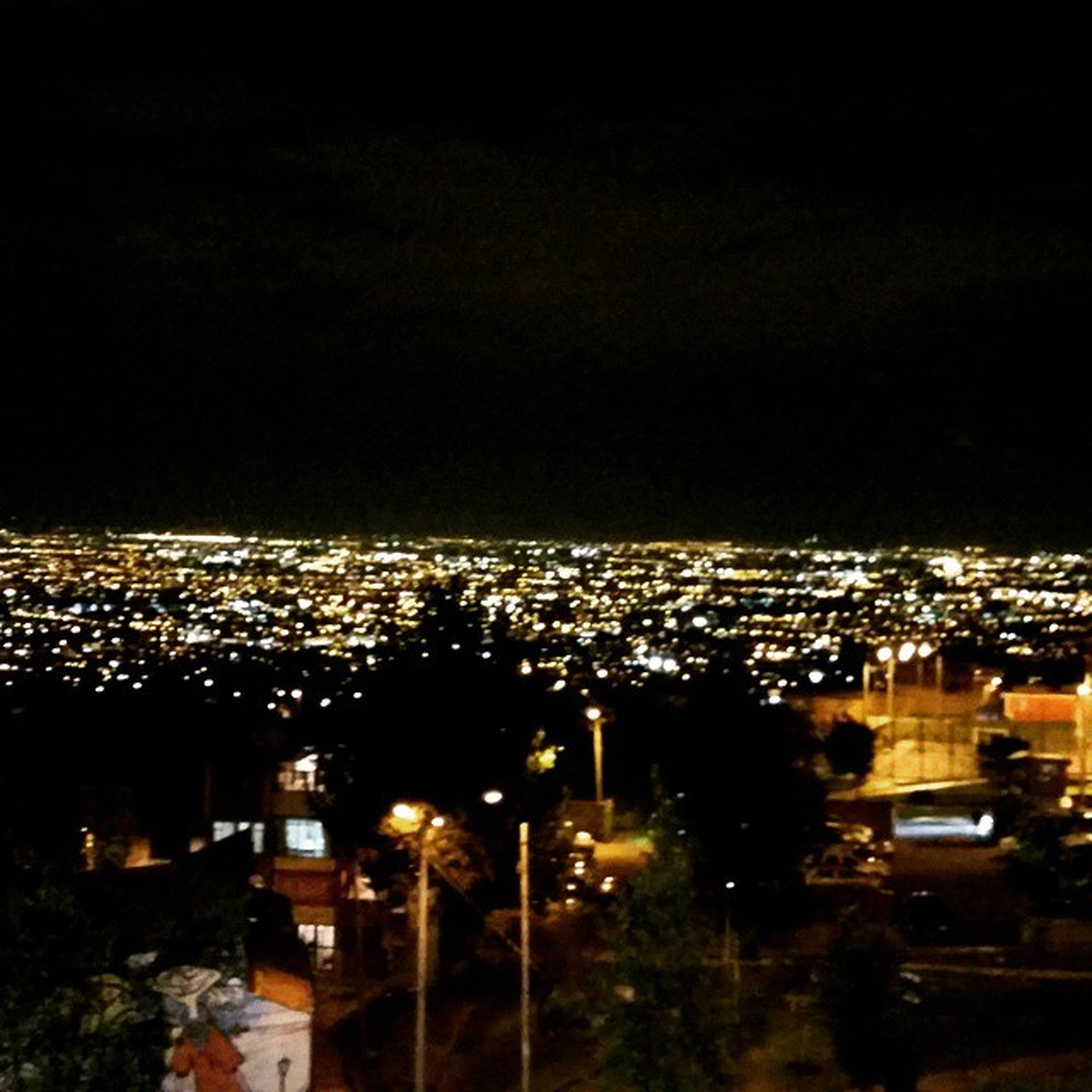 cityscape, city, building exterior, illuminated, crowded, architecture, night, built structure, high angle view, residential district, residential building, aerial view, city life, residential structure, sky, copy space, clear sky, skyscraper, no people, outdoors