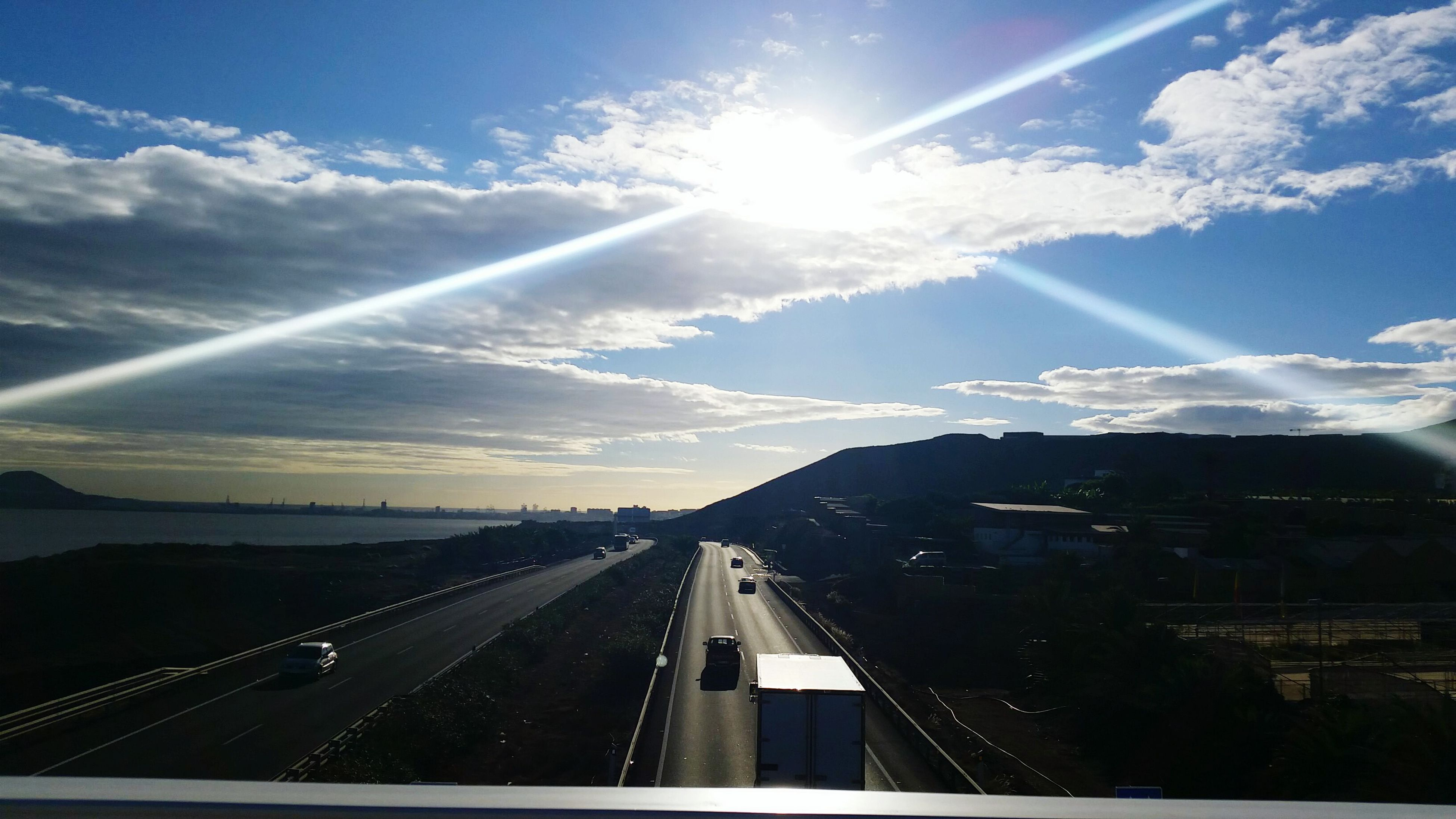 transportation, sunbeam, sky, sun, sunlight, the way forward, vanishing point, cloud - sky, mode of transport, diminishing perspective, lens flare, road, cloud, travel, highway, on the move, journey, nature, glass - material, day