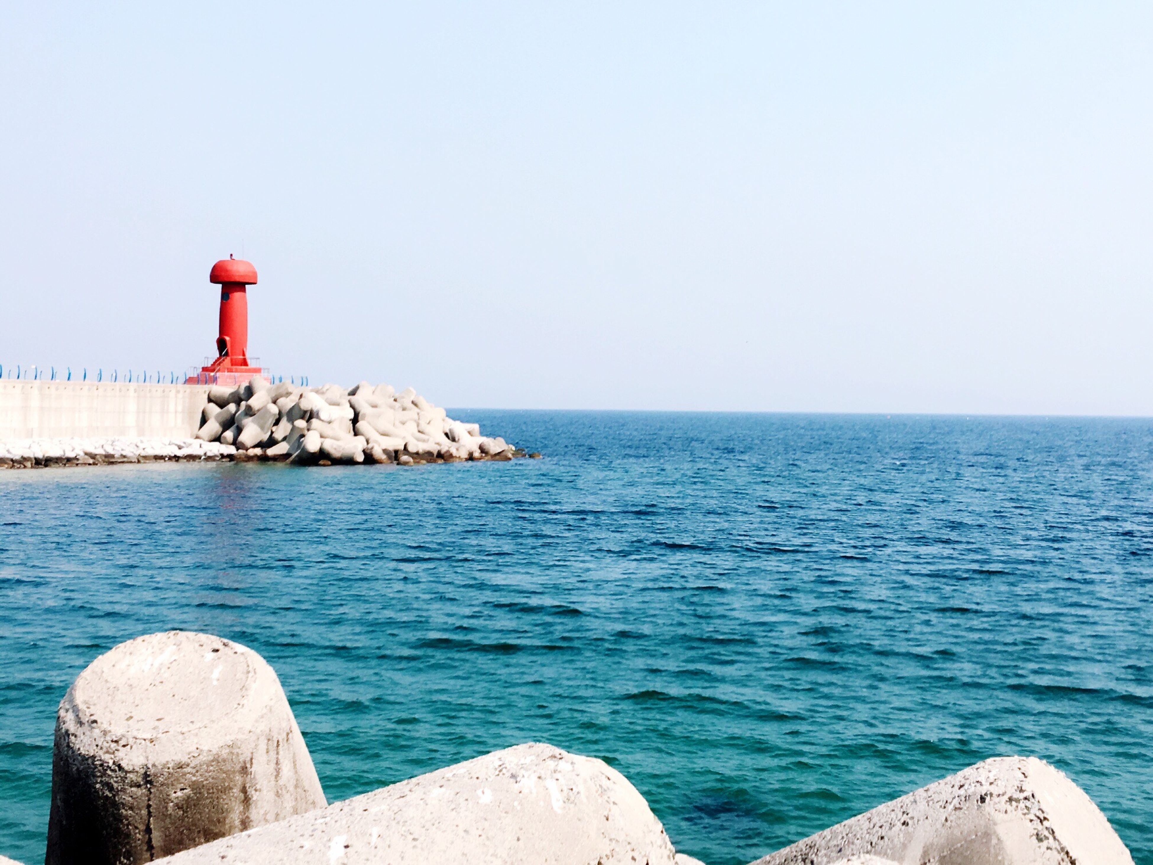 sea, lighthouse, water, horizon over water, guidance, clear sky, copy space, direction, protection, tranquil scene, built structure, scenics, architecture, safety, blue, rock - object, tranquility, beauty in nature, building exterior, nature