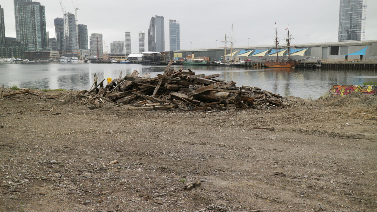A pile of wooden beams is all the remains of old dockland sheds, taken down to make way for an expanding city. Architecture Building Exterior Built Structure City Day Destroyed Docklands Docks Environmental Issues Forgotten Hazy Days Natural Disaster Nature Neglected No People Old Boat Outdoors Post Apocalyptic Sheds Sky Timber Water Wood Pile