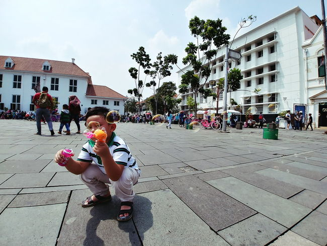 Full Length Childhood People Child Building Exterior Day Outdoors Boys Children Only Playing City Sitting Sky Adult Architecture Tree One Person Gun Toy Toy Bubble Gun Bubbles Large Group Of People Building Kid Historical Building EyeEmNewHere