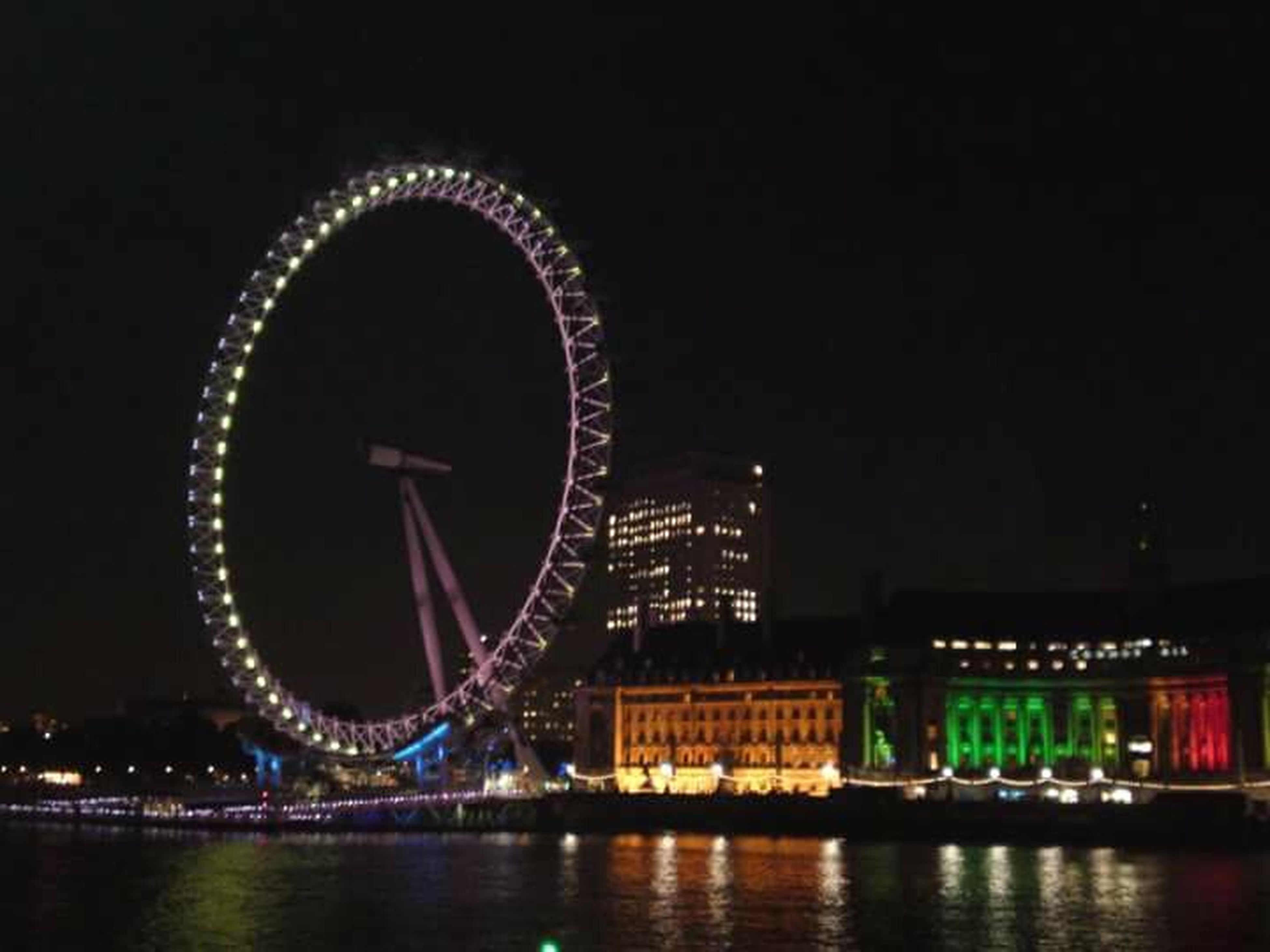 illuminated, night, built structure, architecture, building exterior, water, river, arts culture and entertainment, waterfront, city, ferris wheel, reflection, travel destinations, sky, amusement park, clear sky, lighting equipment, glowing, copy space, famous place