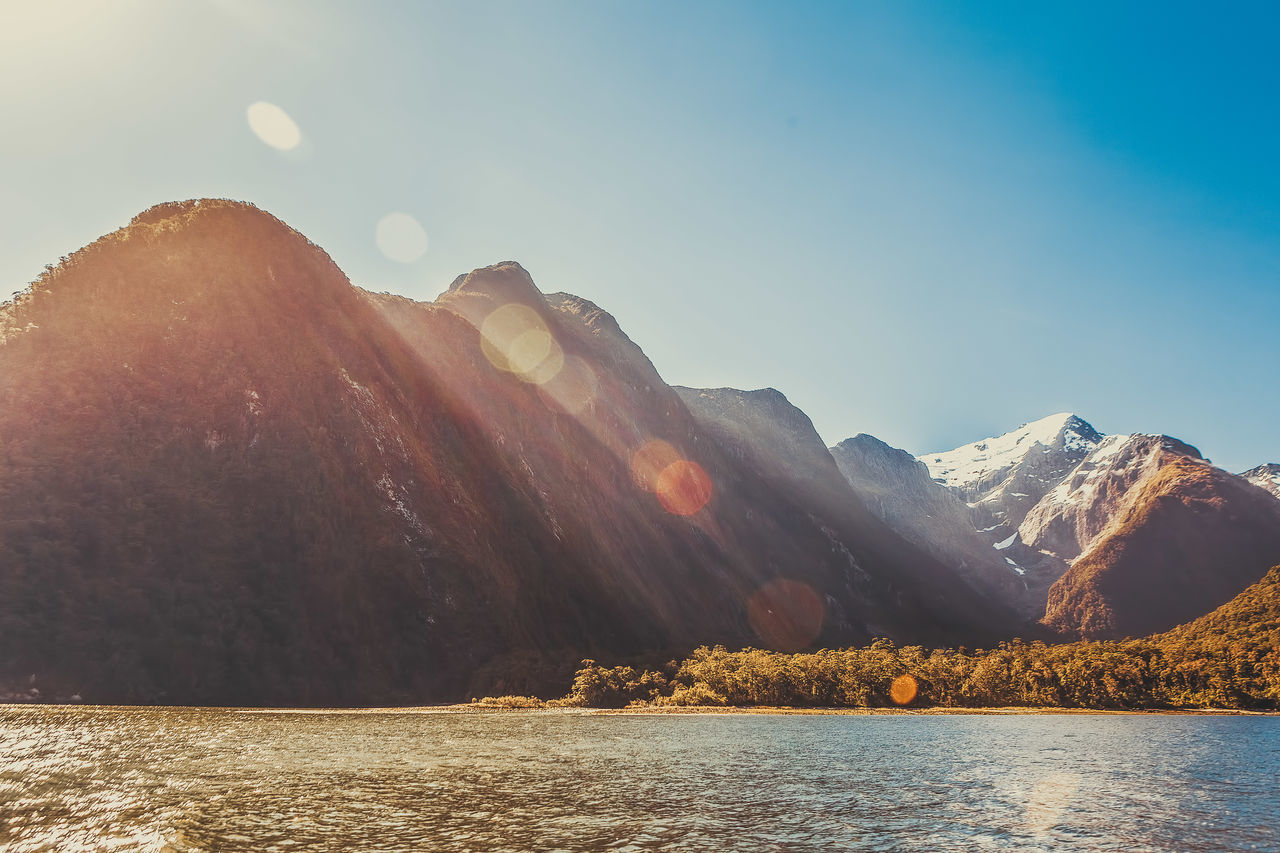 Majestic snow capped peaks of Milford Sound with sun flare. Fiordland, New Zealand Beauty In Nature Day Fiordland Lake Landscape Milford Sound Mountain Mountain Range Nature New Zealand No People Outdoors Scenics Sky Sunlight Tranquil Scene Tranquility Tree Water Waterfront