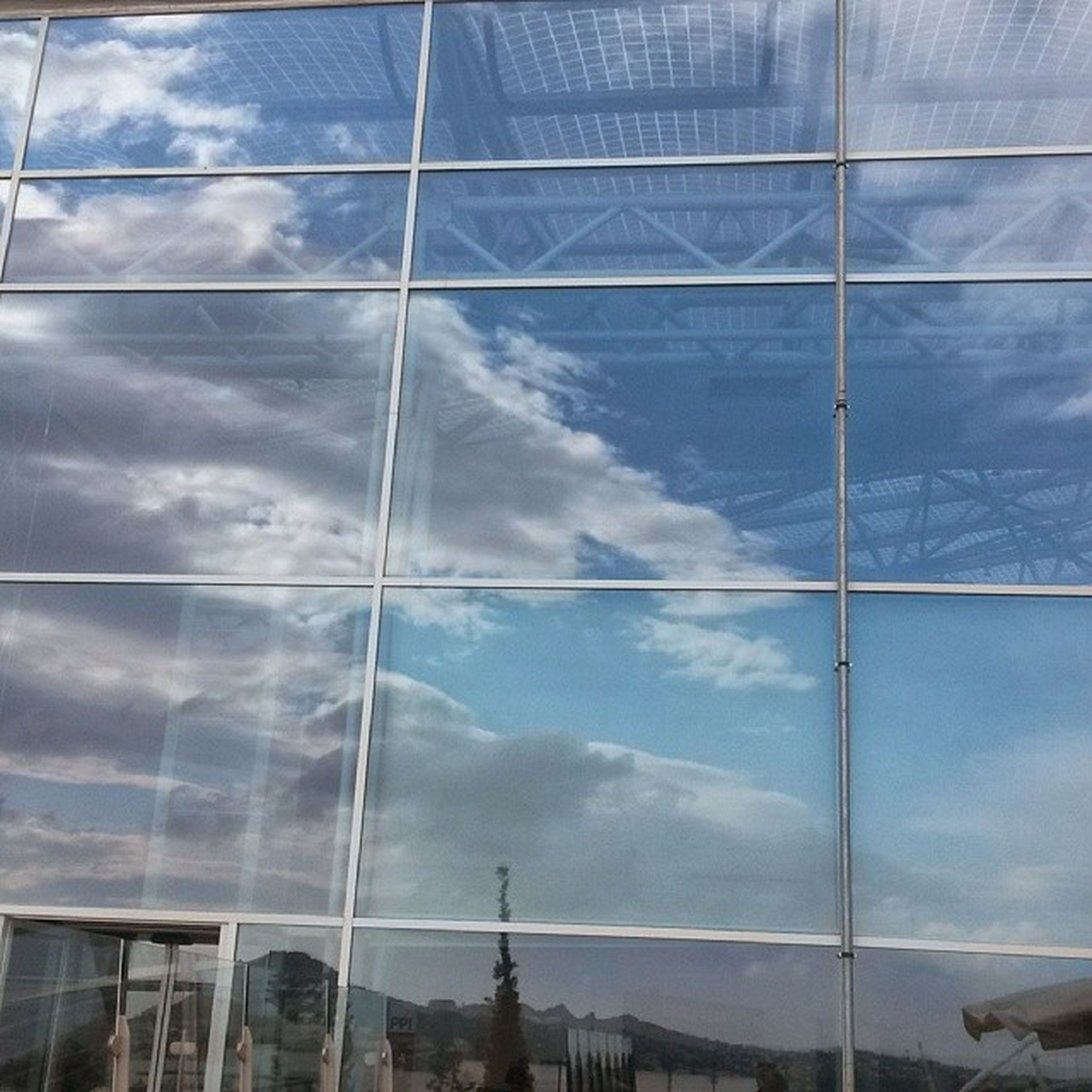 sky, architecture, built structure, low angle view, cloud - sky, glass - material, building exterior, modern, blue, reflection, cloud, cloudy, day, window, building, no people, transparent, glass, city, outdoors