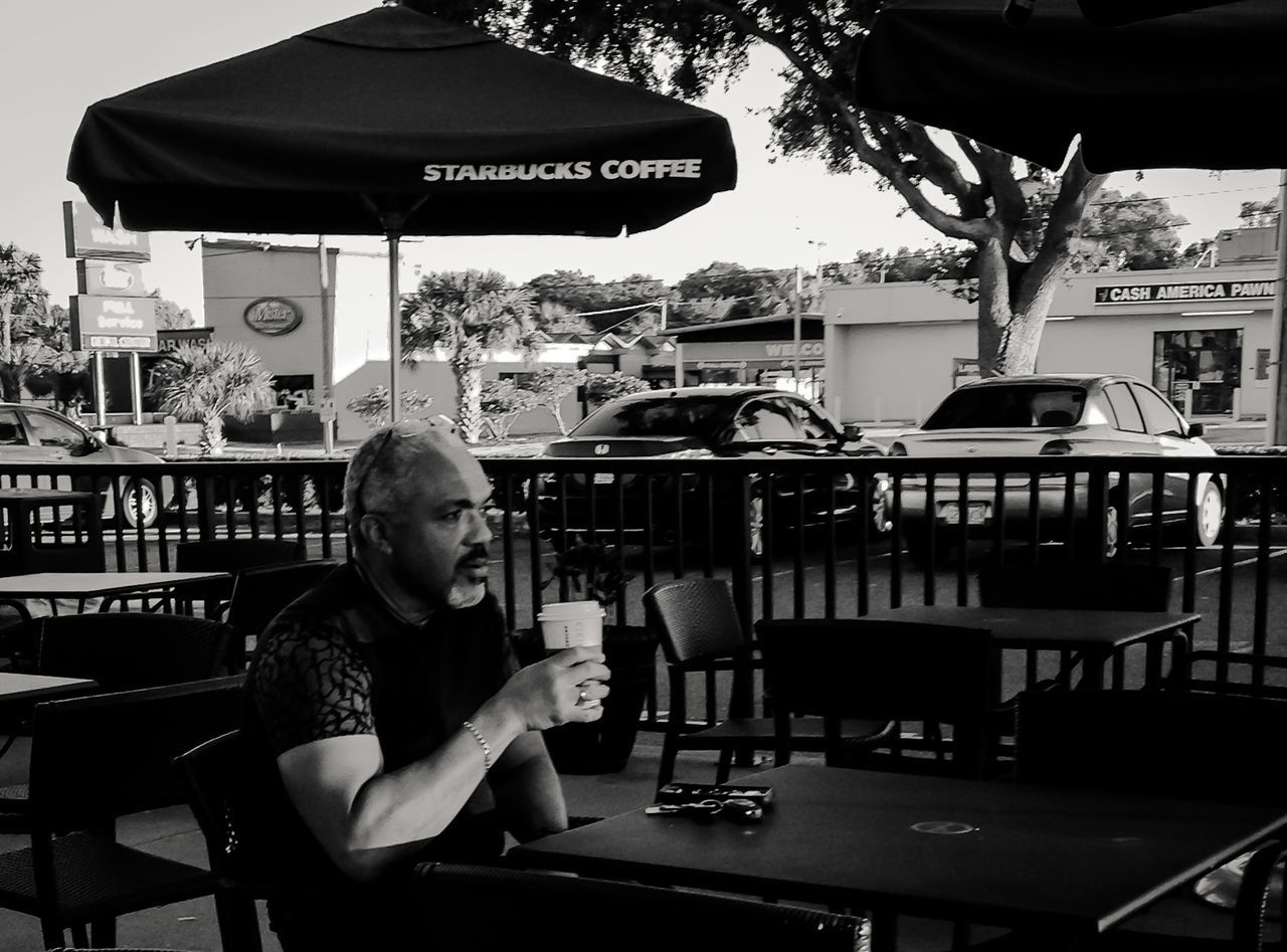 drink, real people, food and drink, one person, refreshment, cafe, communication, holding, leisure activity, young adult, lifestyles, day, bad habit, outdoors, freshness, people
