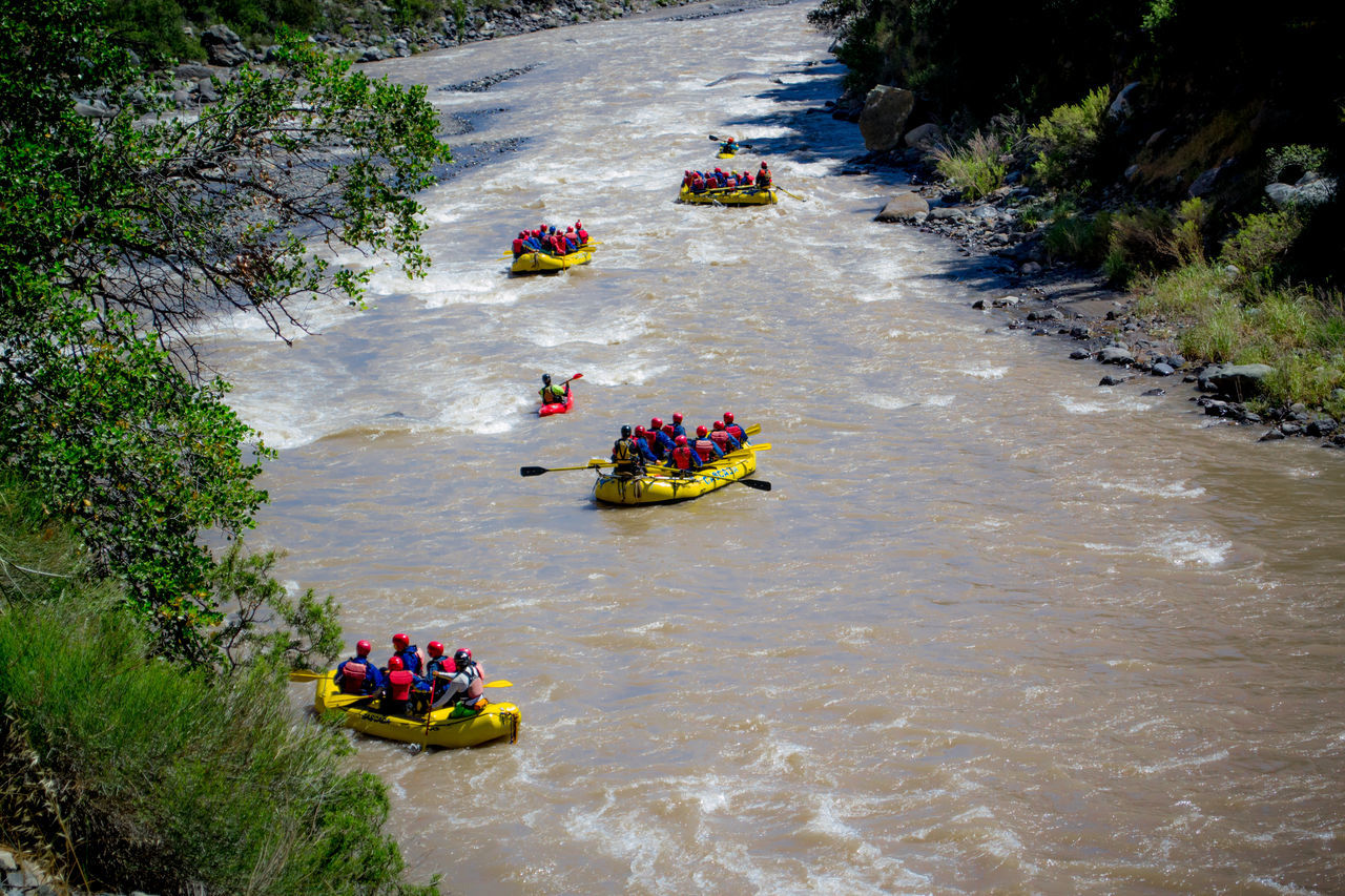 rafting, real people, large group of people, adventure, river, leisure activity, high angle view, men, water, teamwork, women, inflatable raft, lifestyles, enjoyment, preparation, day, togetherness, sport, raft, outdoors, skill, nature, adult, people