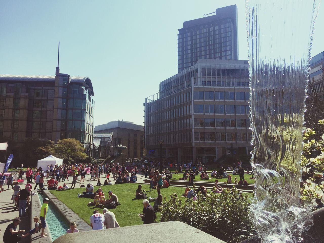 architecture, building exterior, built structure, large group of people, city, modern, skyscraper, outdoors, day, real people, grass, crowd, sky, people