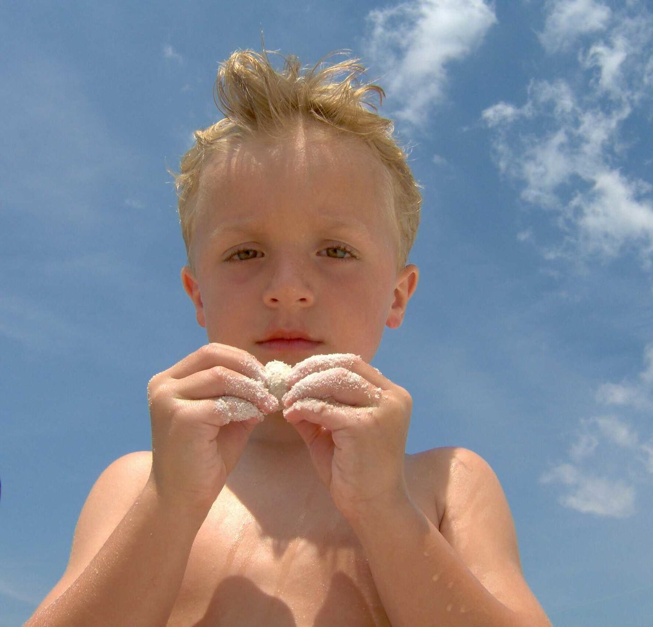 Low Angle Portrait Of Shirtless Boy Holding Sand Covered Seashell