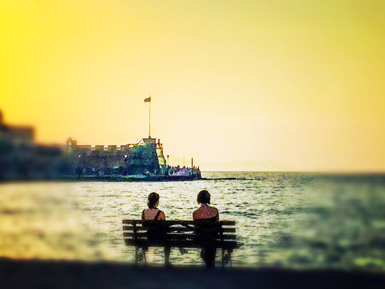 water, sea, leisure activity, sunset, two people, nature, togetherness, men, sitting, beauty in nature, sky, lifestyles, real people, clear sky, outdoors, built structure, scenics, women, architecture, day, people