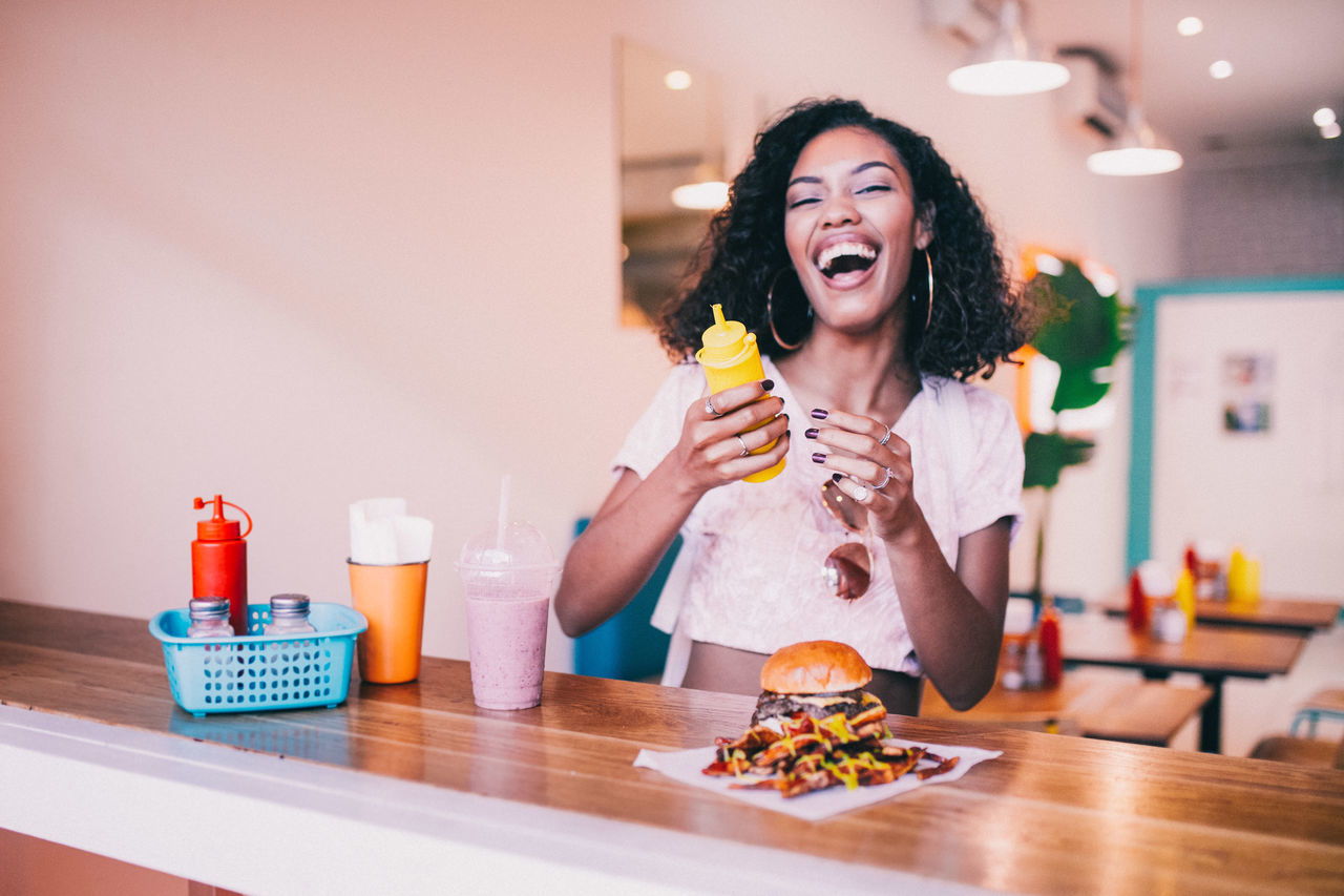 Bottle Burger Burgerbar Domestic Life Eating Food Food And Drink Freshness Fries Front View Hamburger Holding Indoors  Junk Food Lifestyles One Person Real People Table Unhealthy Eating Young Adult