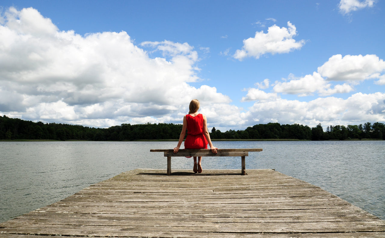 blond girl in red dress sitting on the bench on wooden pier t the lakeside in Poland Adult Bench Blonde Cloud Day Full Length Lake Nature One Person Pier Rear View Red Dress Sky Sky And Clouds Summer Tranquil Scene Tranquility Water Woman Wooden
