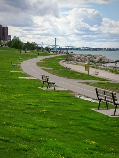 Lonely benches- Benches Benches_Of_The_World_Unite Benchinthepark Natural Light Portrait Riverside Detroit River DetroitMichigan Windsor Ontario Green Grass August Showcase Trail Taking Photos Park Solum Beautyineverything My Point Of View Patterns Everywhere Clouds And Sky Cloudy Cloudporn Cloud - Sky River View Riverbank River Collection Adapted To The City The Week On EyeEm
